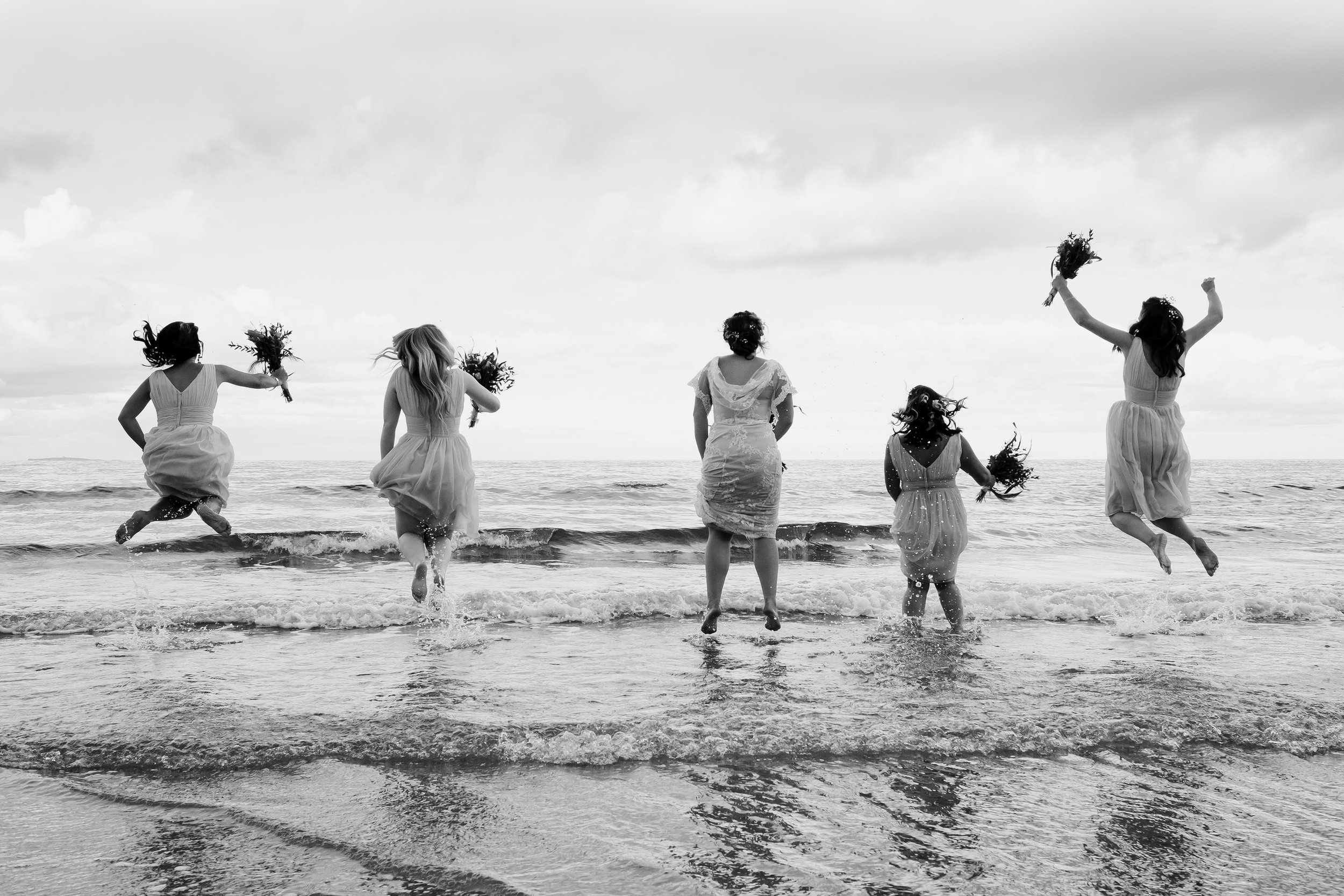 Four bridesmaids and bride jump in the sea.
