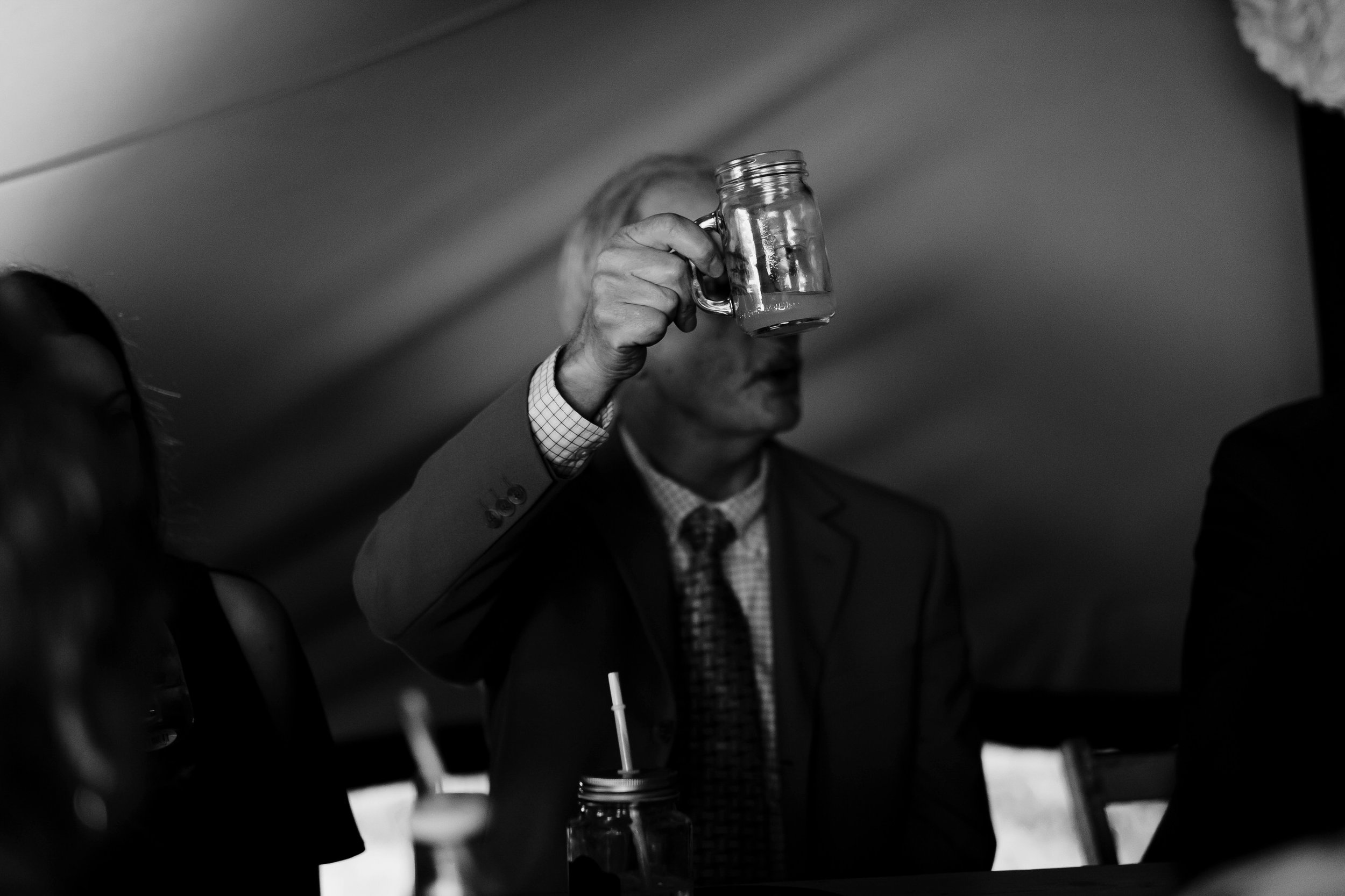 Guest raises a glass to toast groom's following his speech.