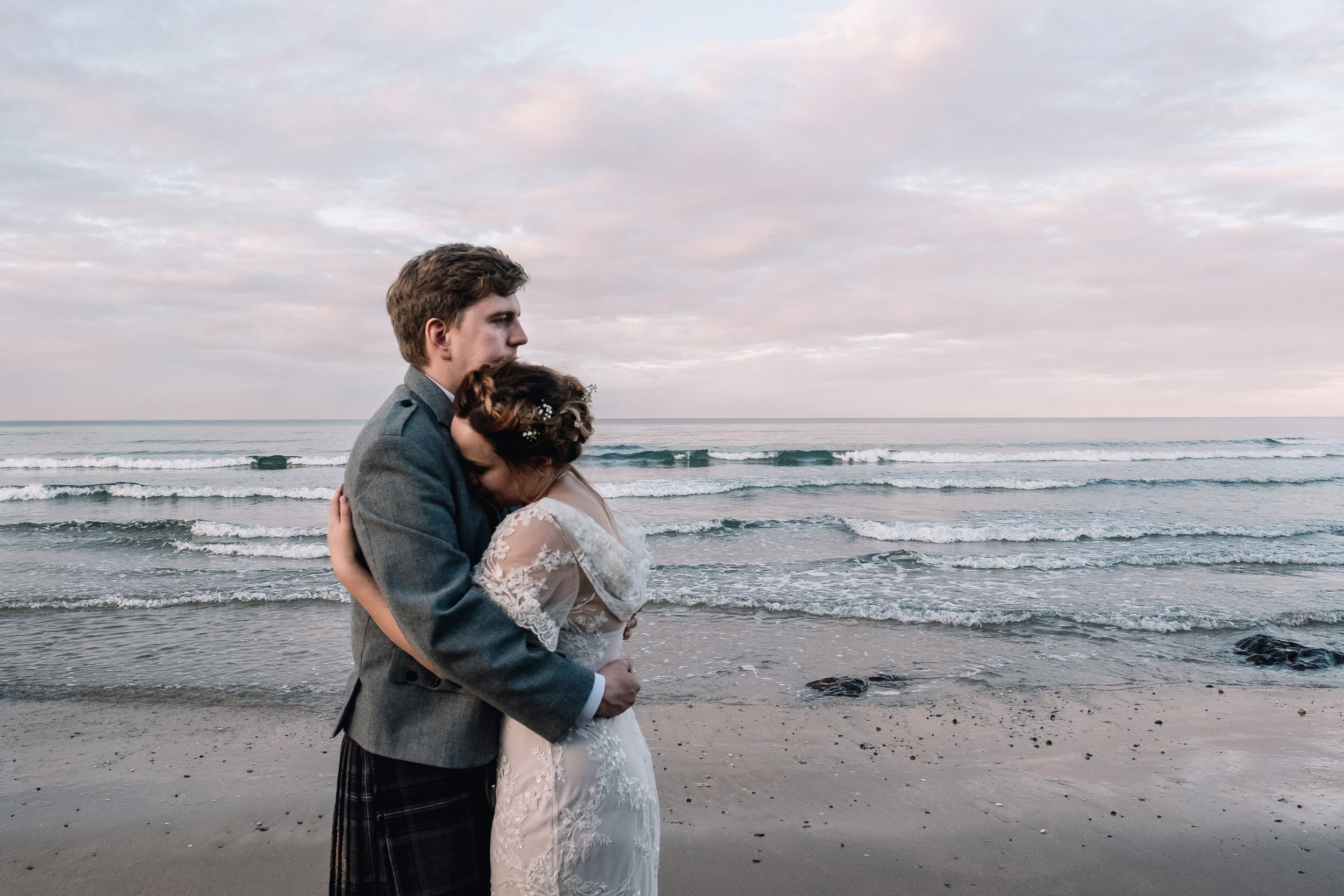 Bride and groom stand hugging at sunset at the beach