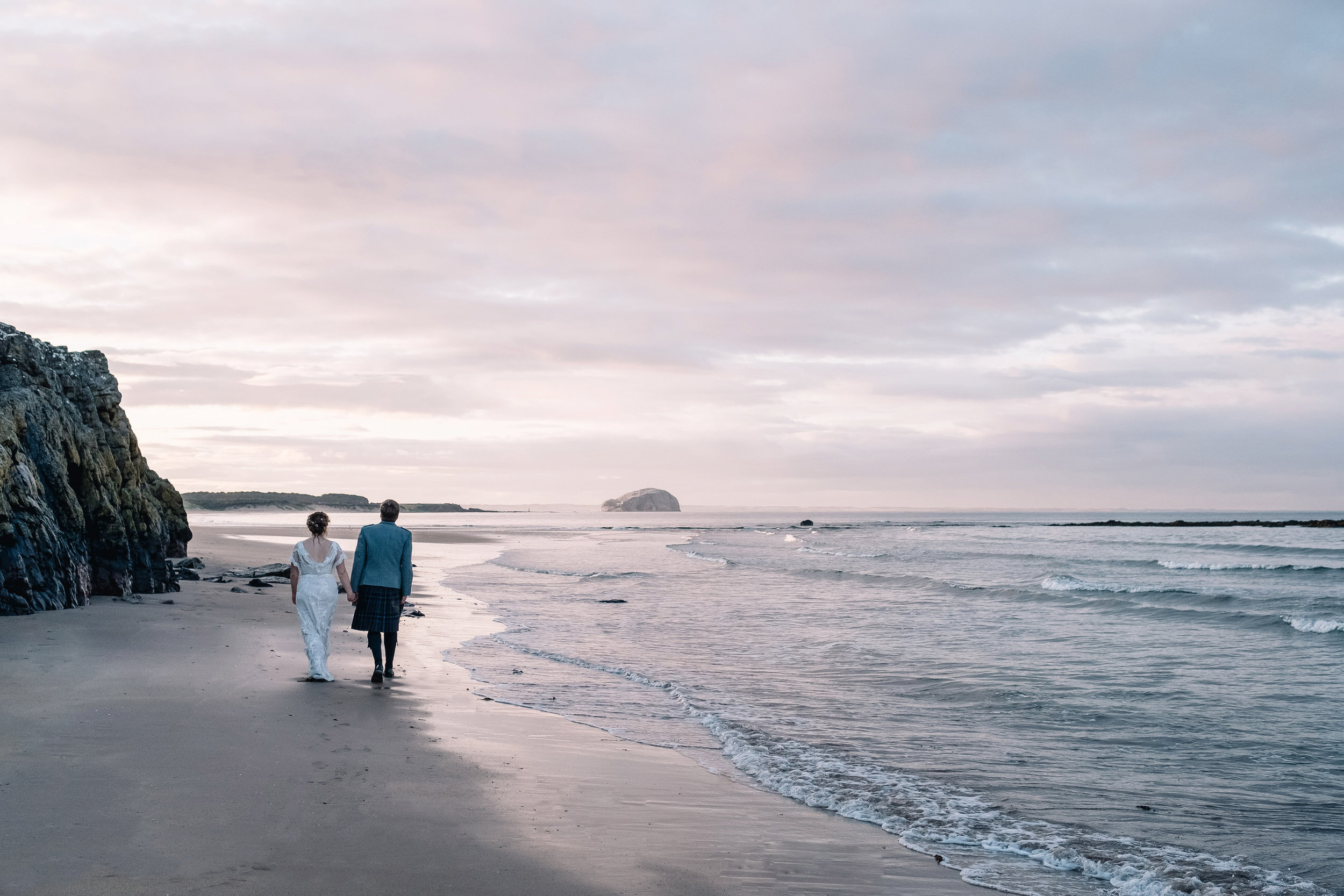 A newly married couple walk on the beach at sunset at th elog cabin at Ravensheugh.