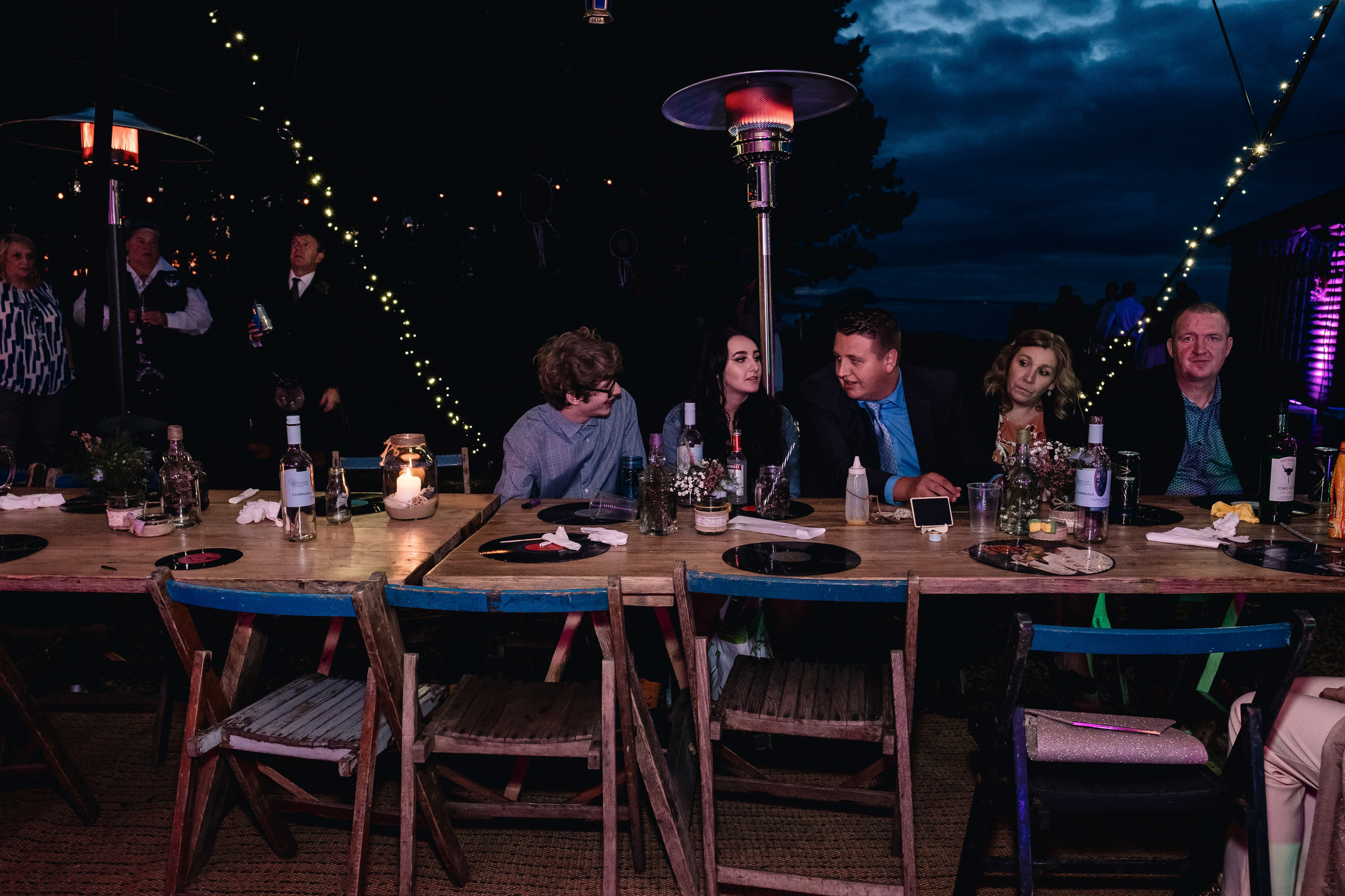 Guests sitting at table at night.