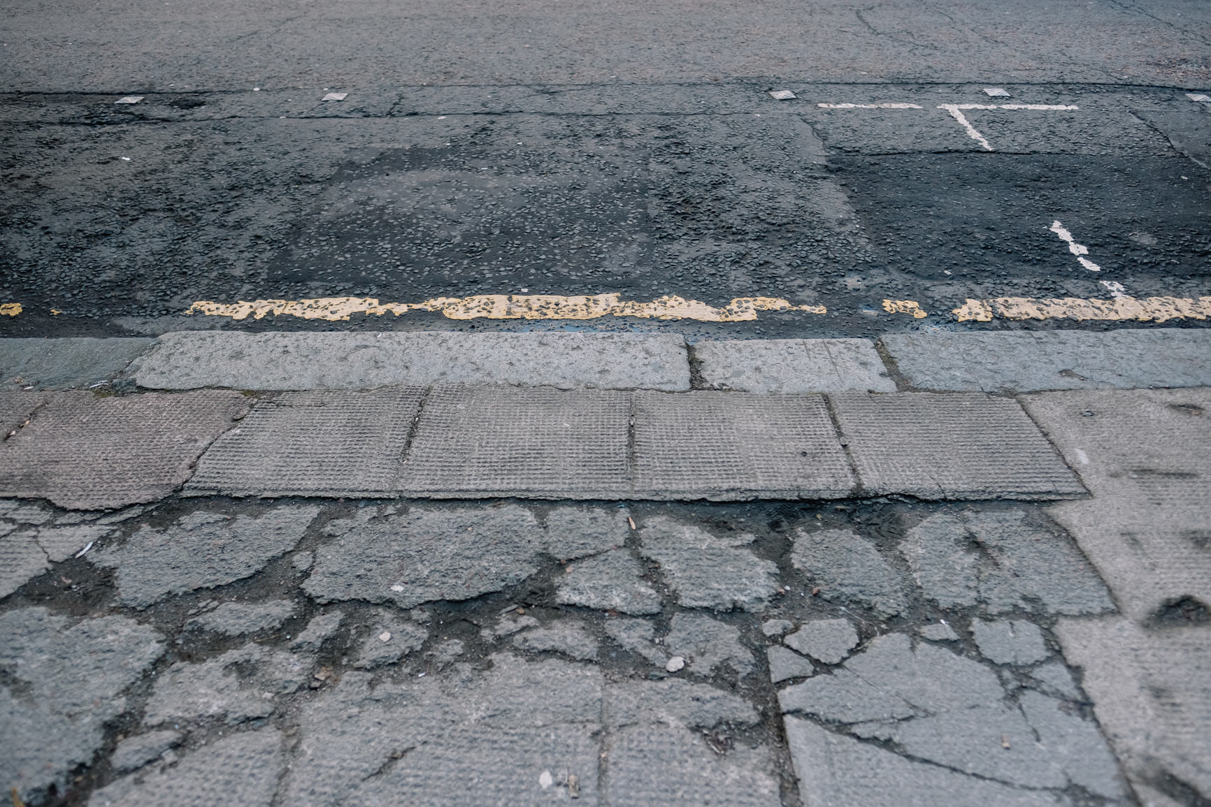 Cracked pavement and yellow lines.
