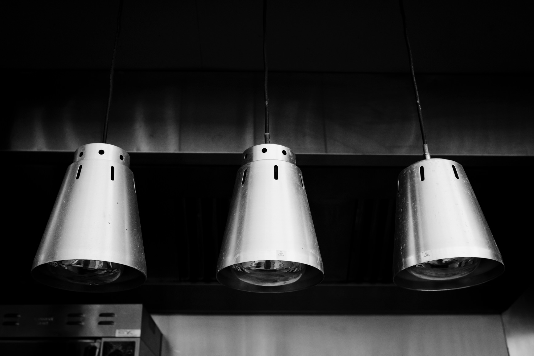 Three steel lampshades hanging from roof of outdoor area.