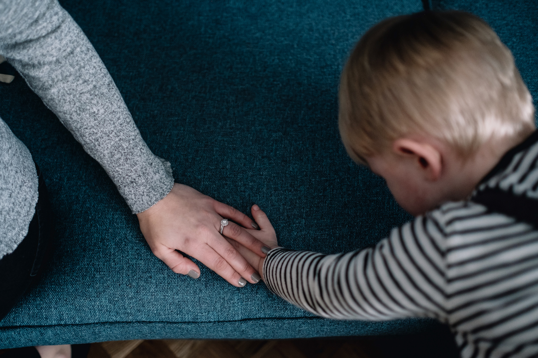 Boy's hand on blue sofa and mother's hand is on top.