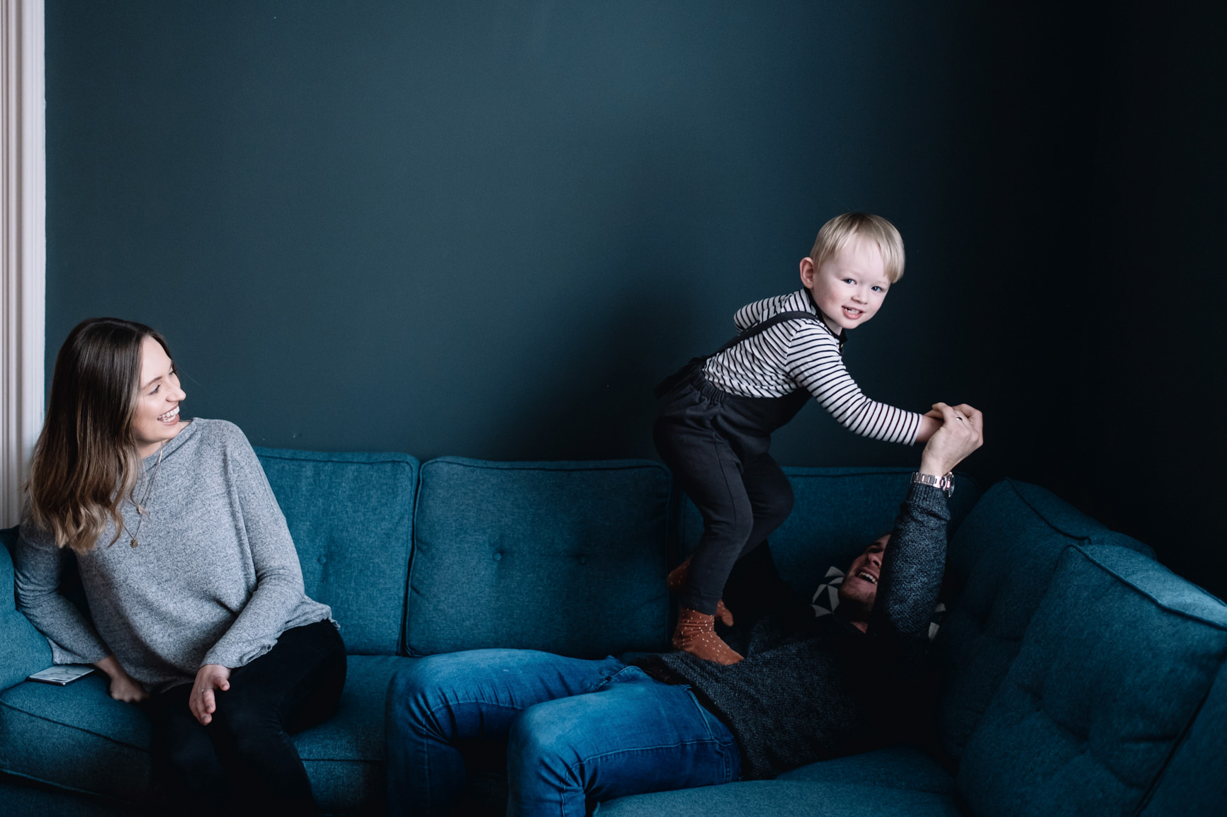 A young boy is jumping on his father's stomach.