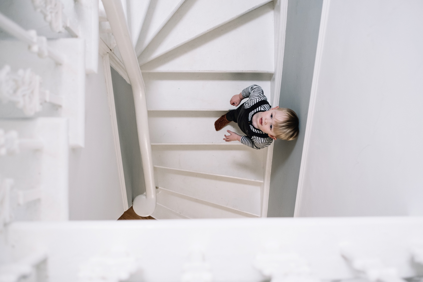 A young boy is walking down a spiral stair case.