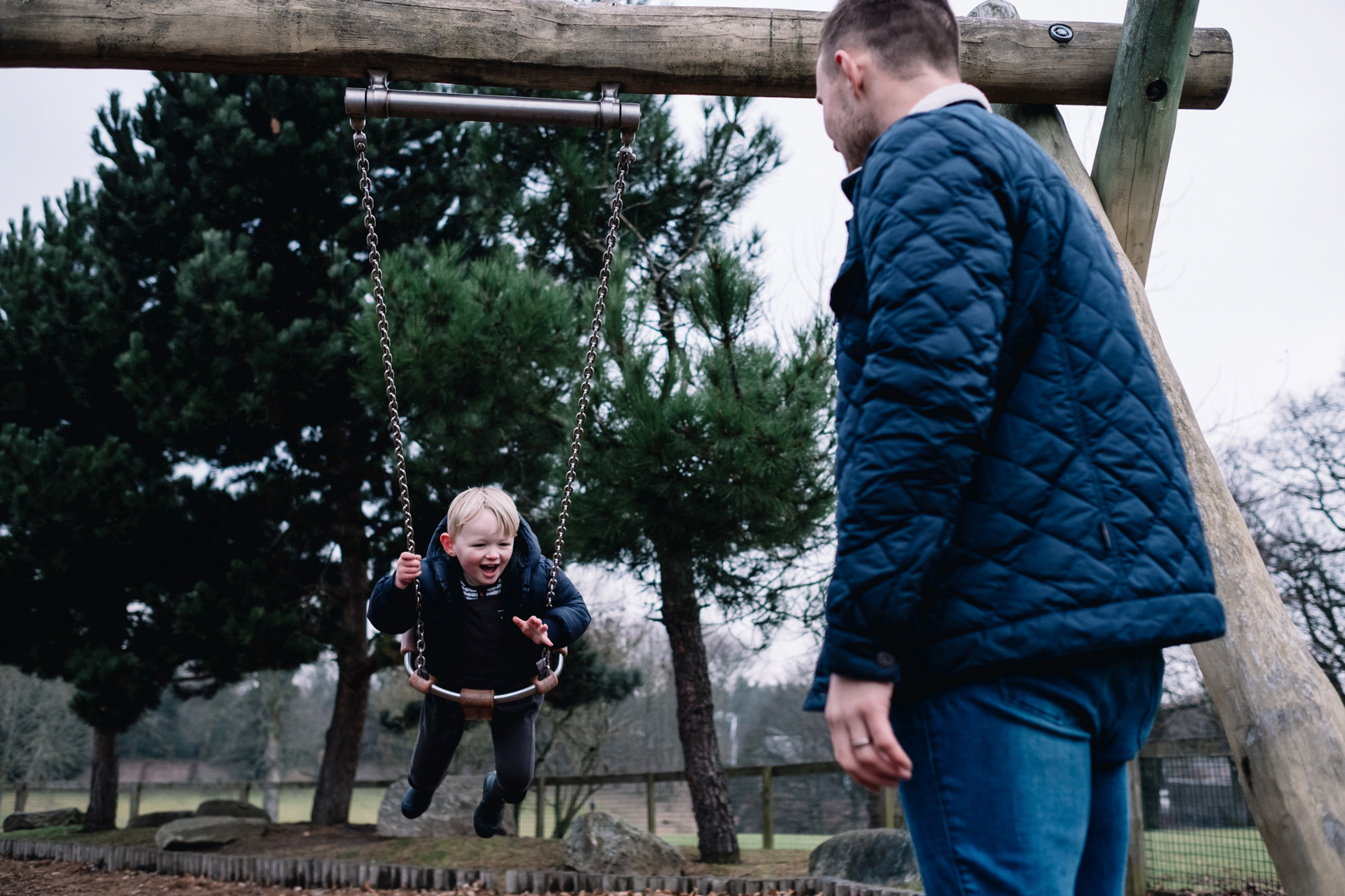 Father stands pushing his son on a swing.