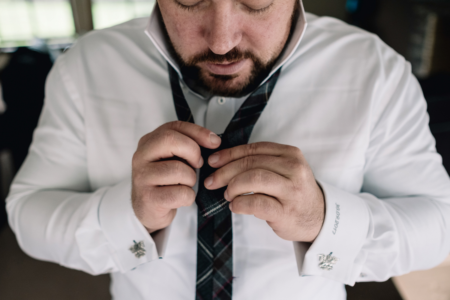 Groom fixing his tie.