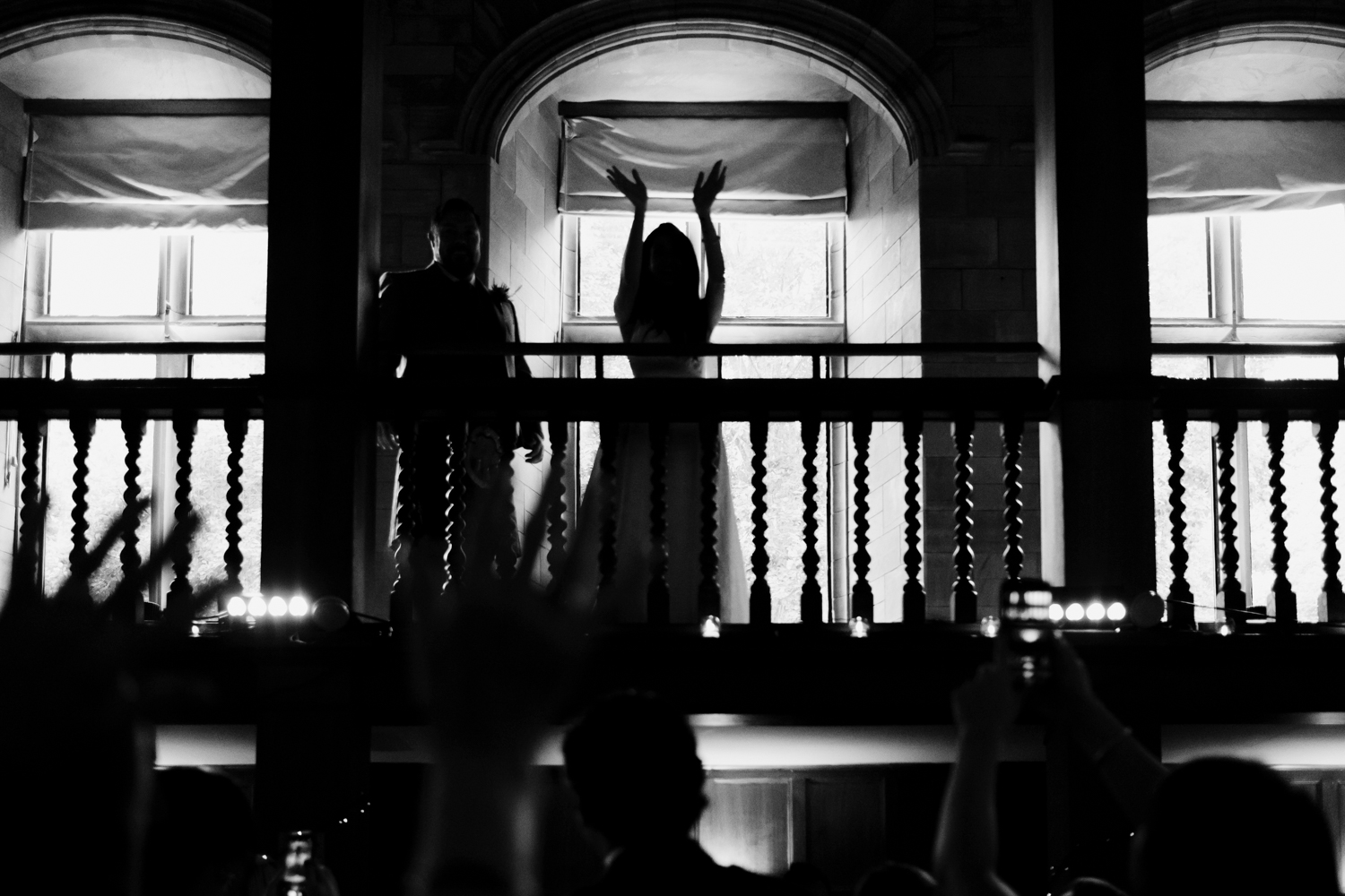 Bride holds hands up and claps from balcony of Achnagairn Estate ballroom.