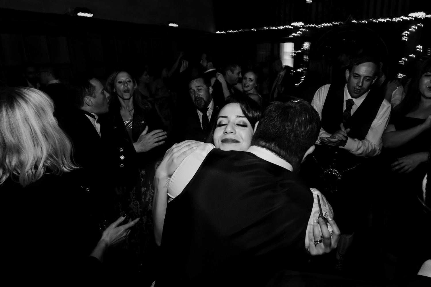 Bride and groom hug on the dance floor.