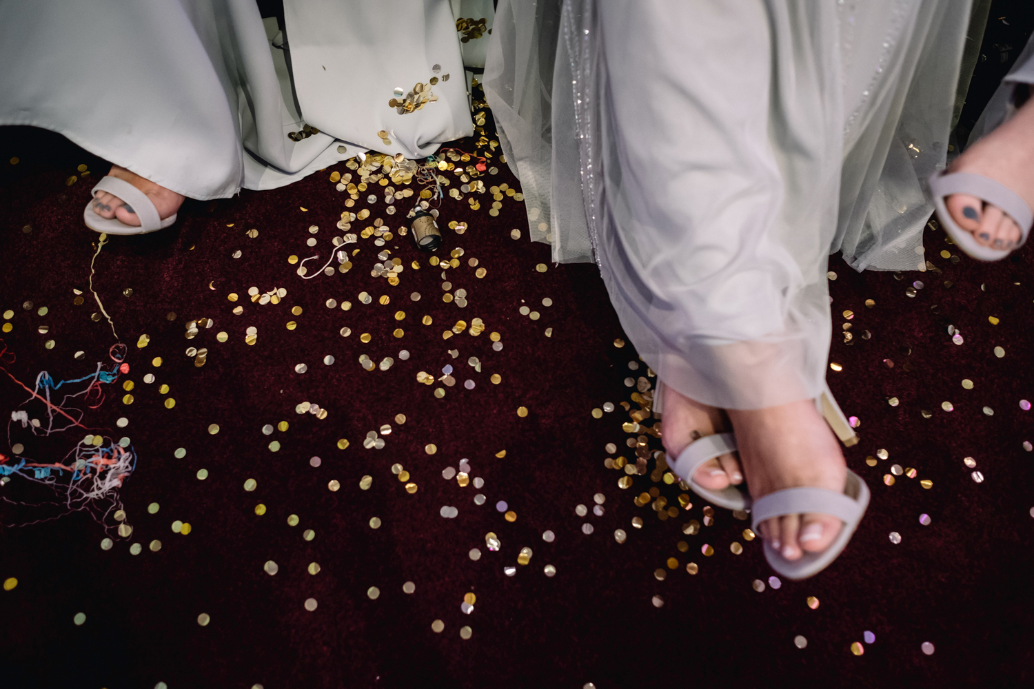 Bridemaids feet and their lavender dresses contrast against a dark red carpet and gold confetti.