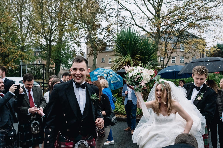 Bride smile + holds her flowers aloft.