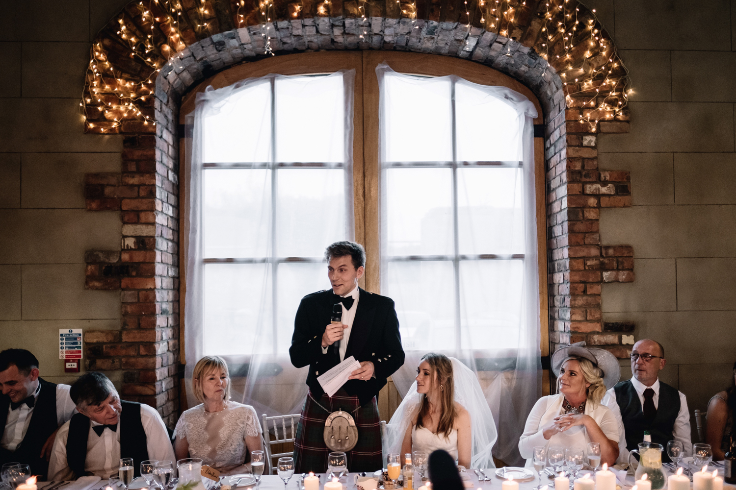 Groom stands and addresses his guests during his speech.