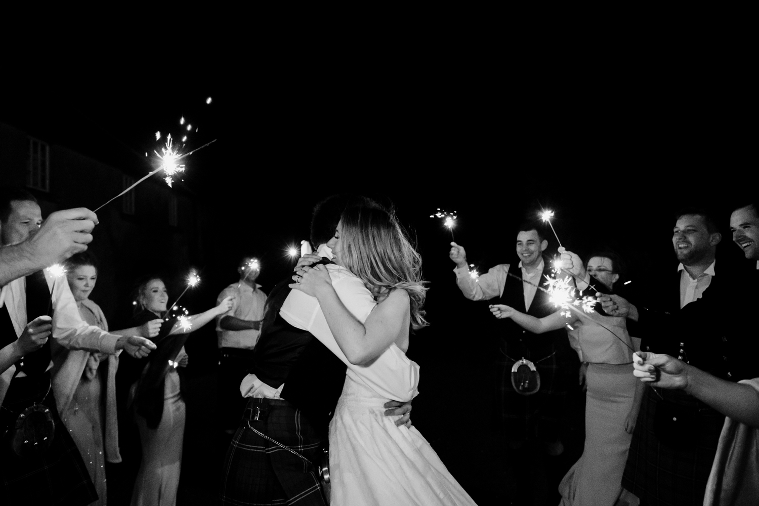 Bride + groom embrace surrounded by the bridal party who hold out sparklers.