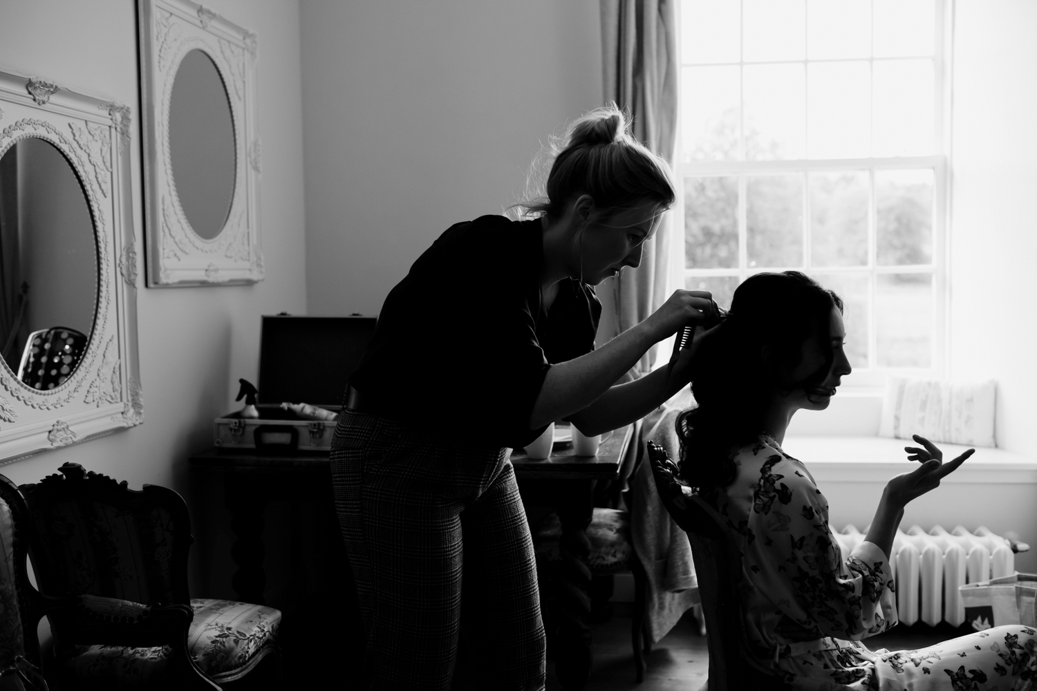 Bride is getting her hair done on the morning of her wedding.