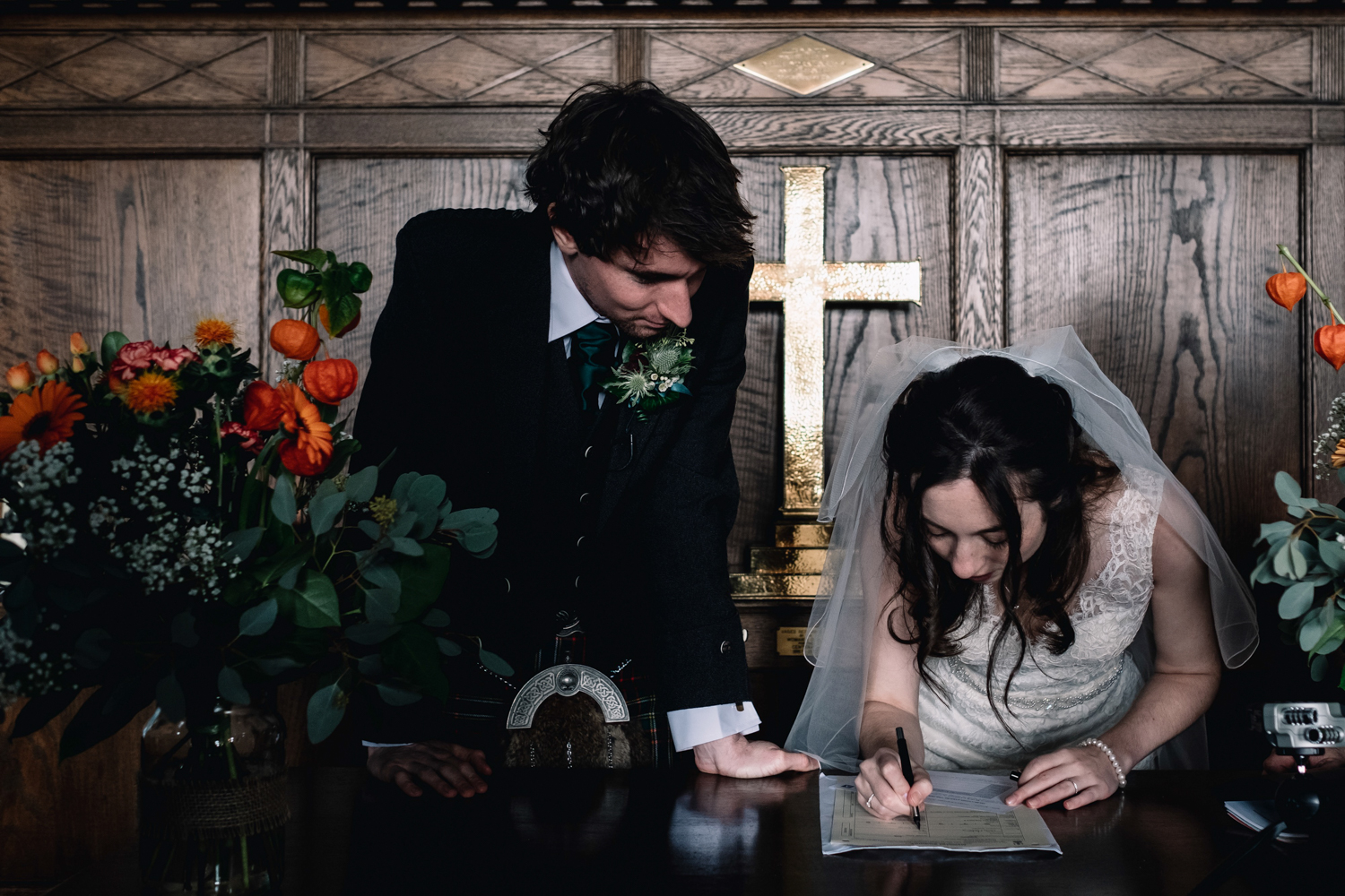 Bride and groom sign the register.