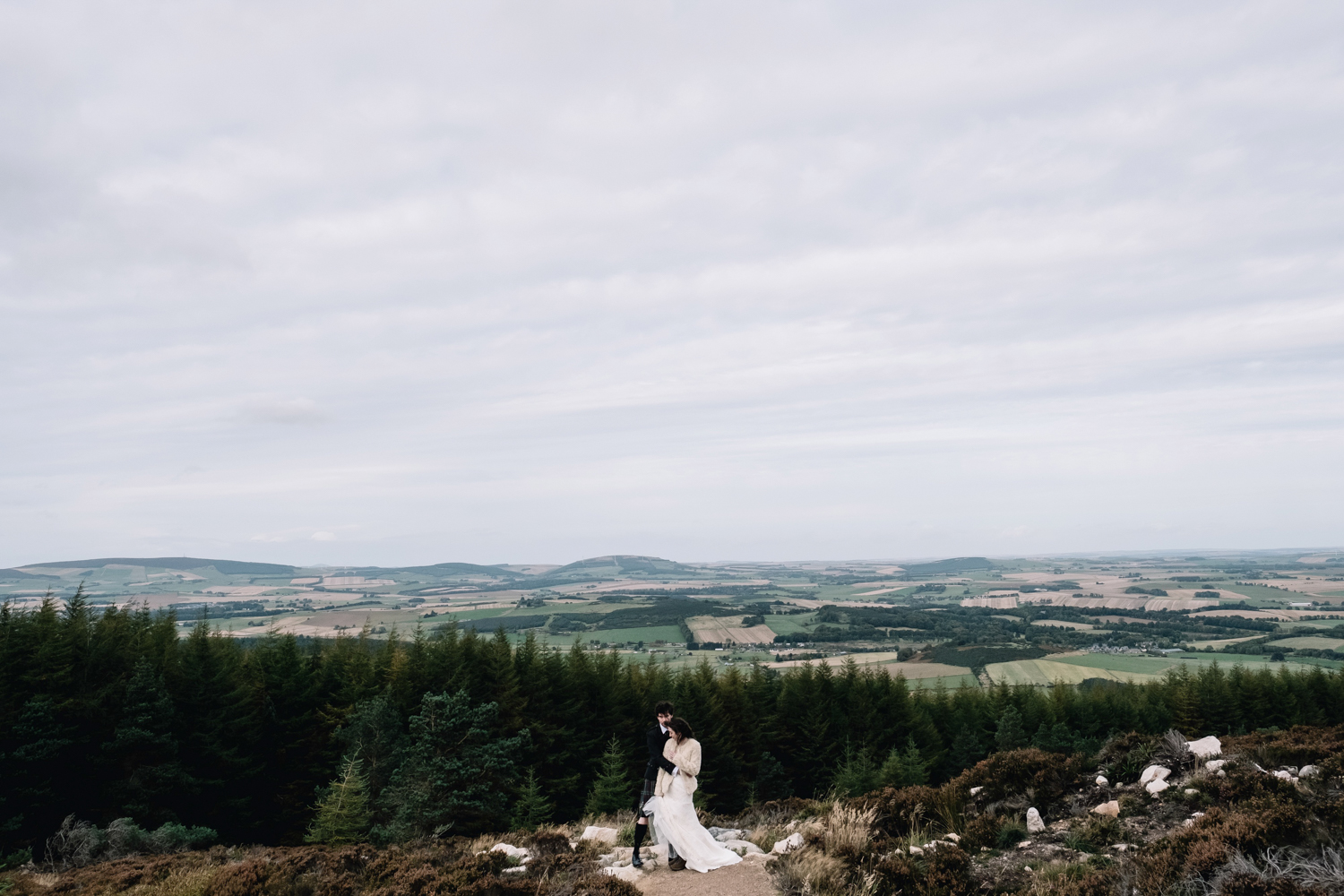 Bride + groom stand on an elevated point of Bennachie.