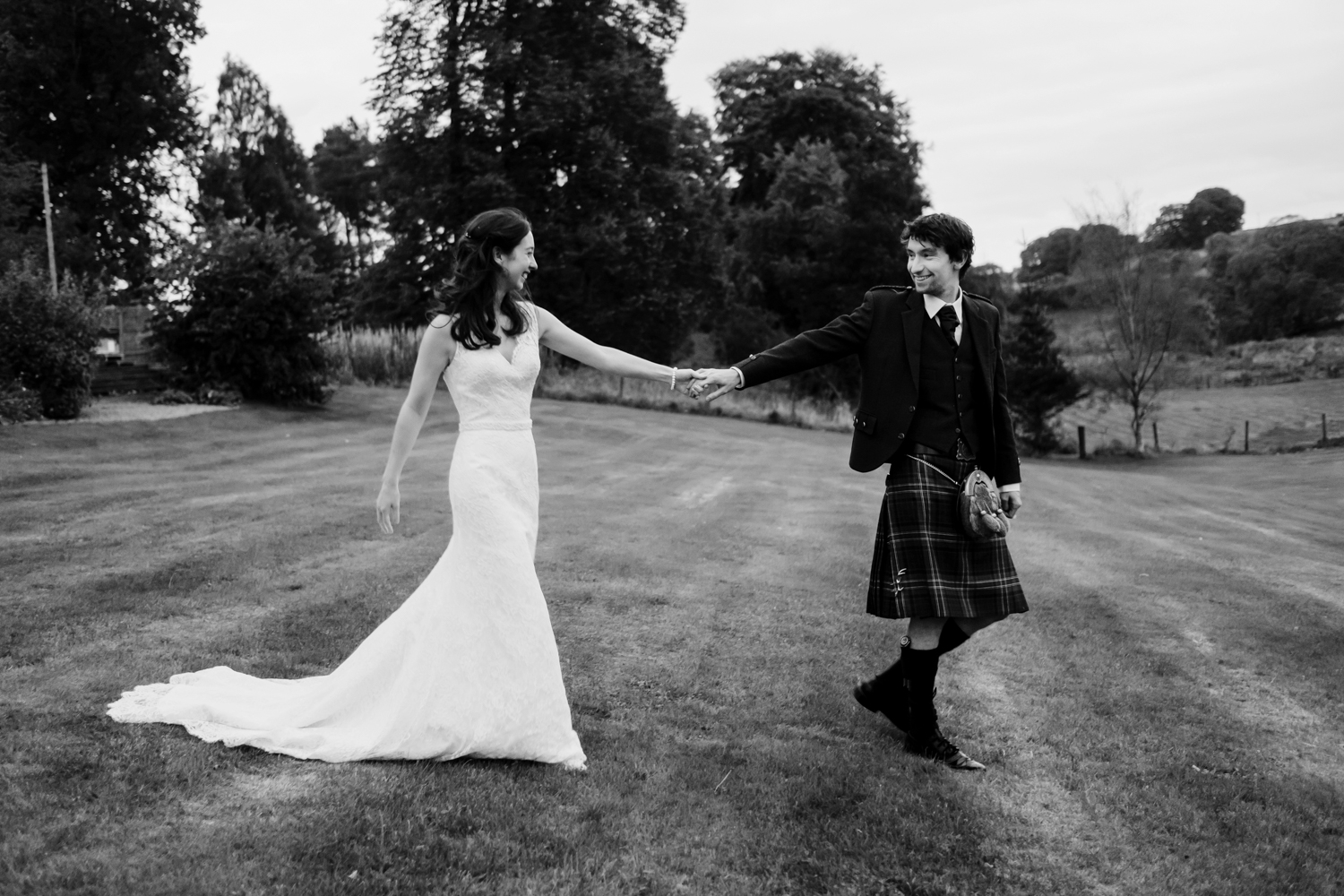 Bride and groom holding hands as they walk apart from each other.
