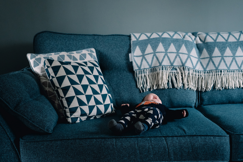 Baby lies on blue sofa.