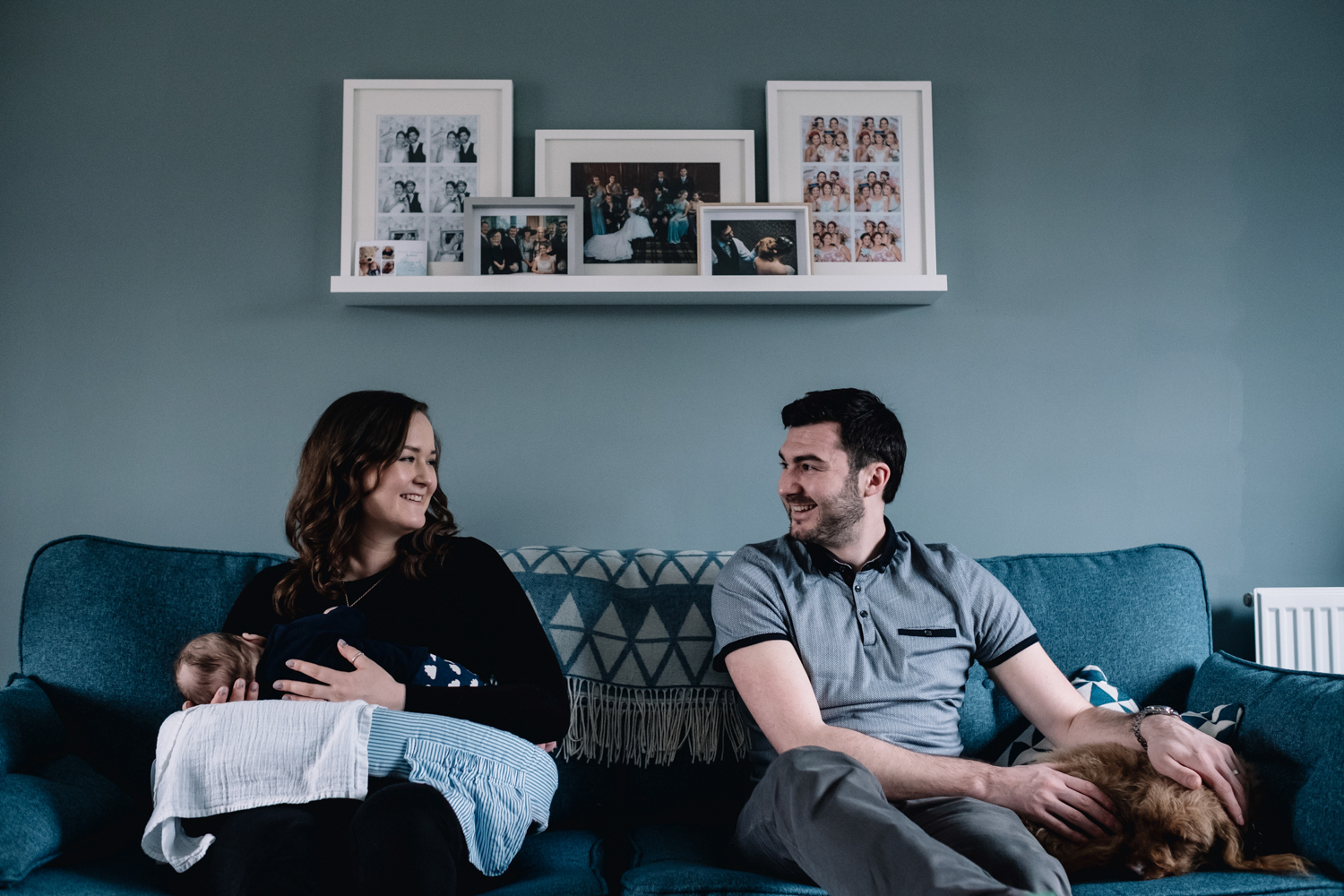 Mother and father sitting on sofa smiling at each other.