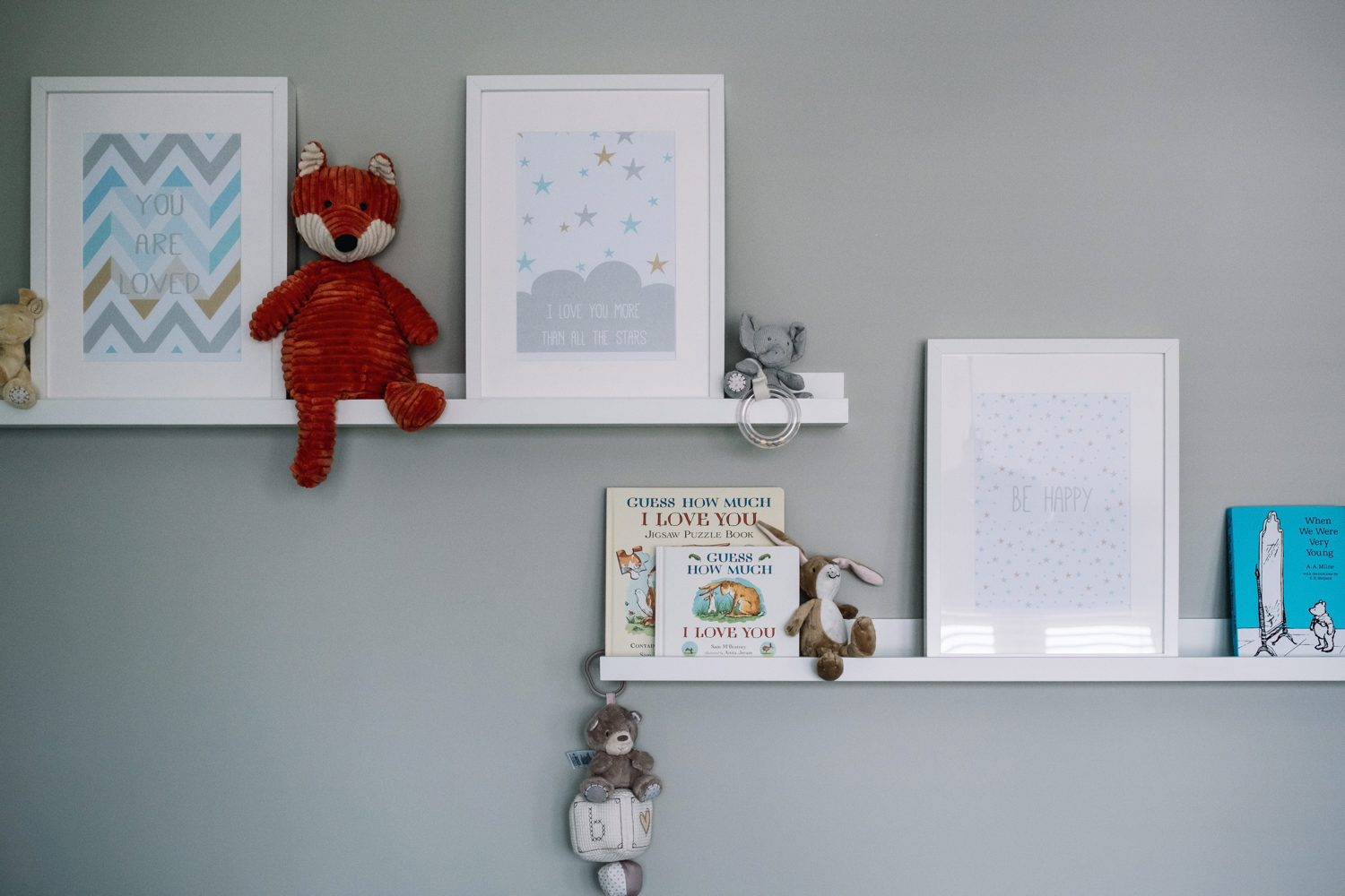 Wall of nursery with prints + books.