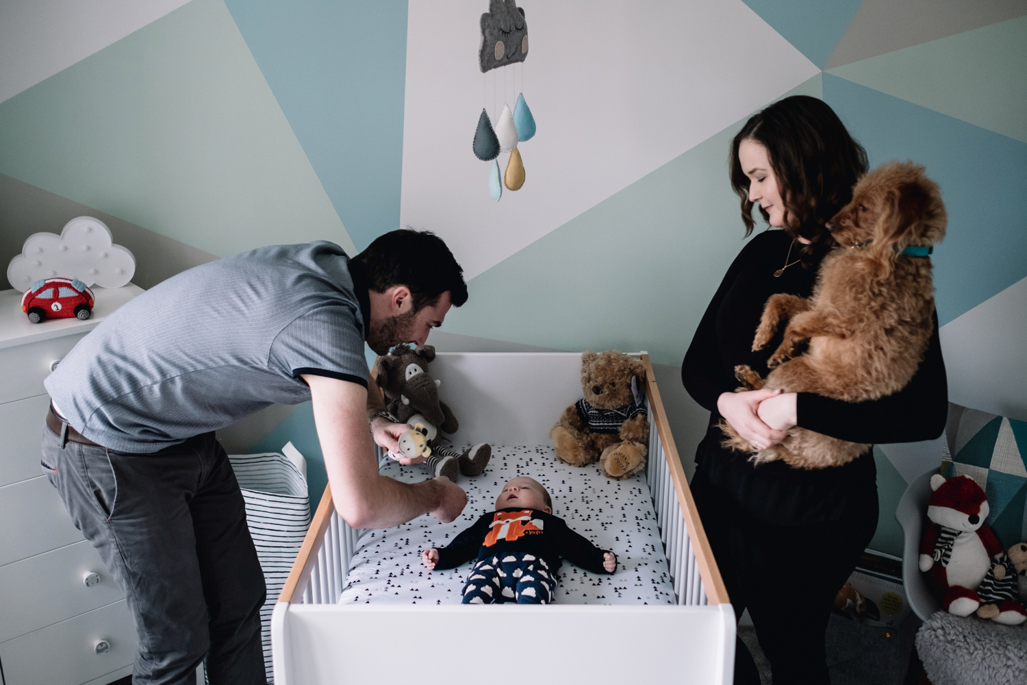 Parents looking at their son who is lying in his cot.