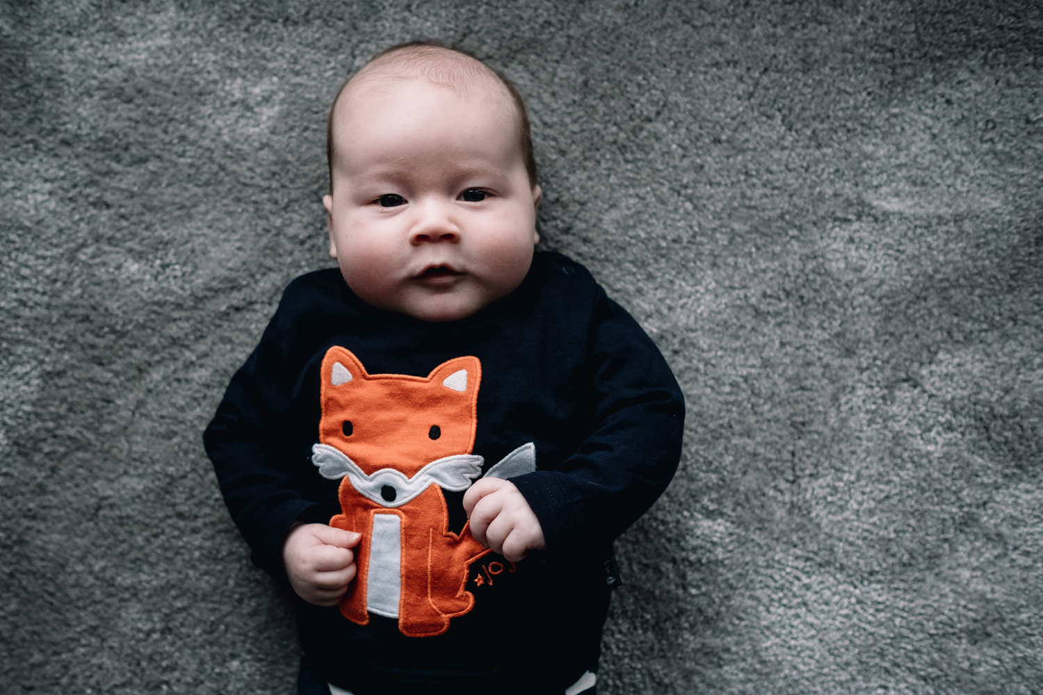Baby wearing fox jumper is looking directly to the camera.