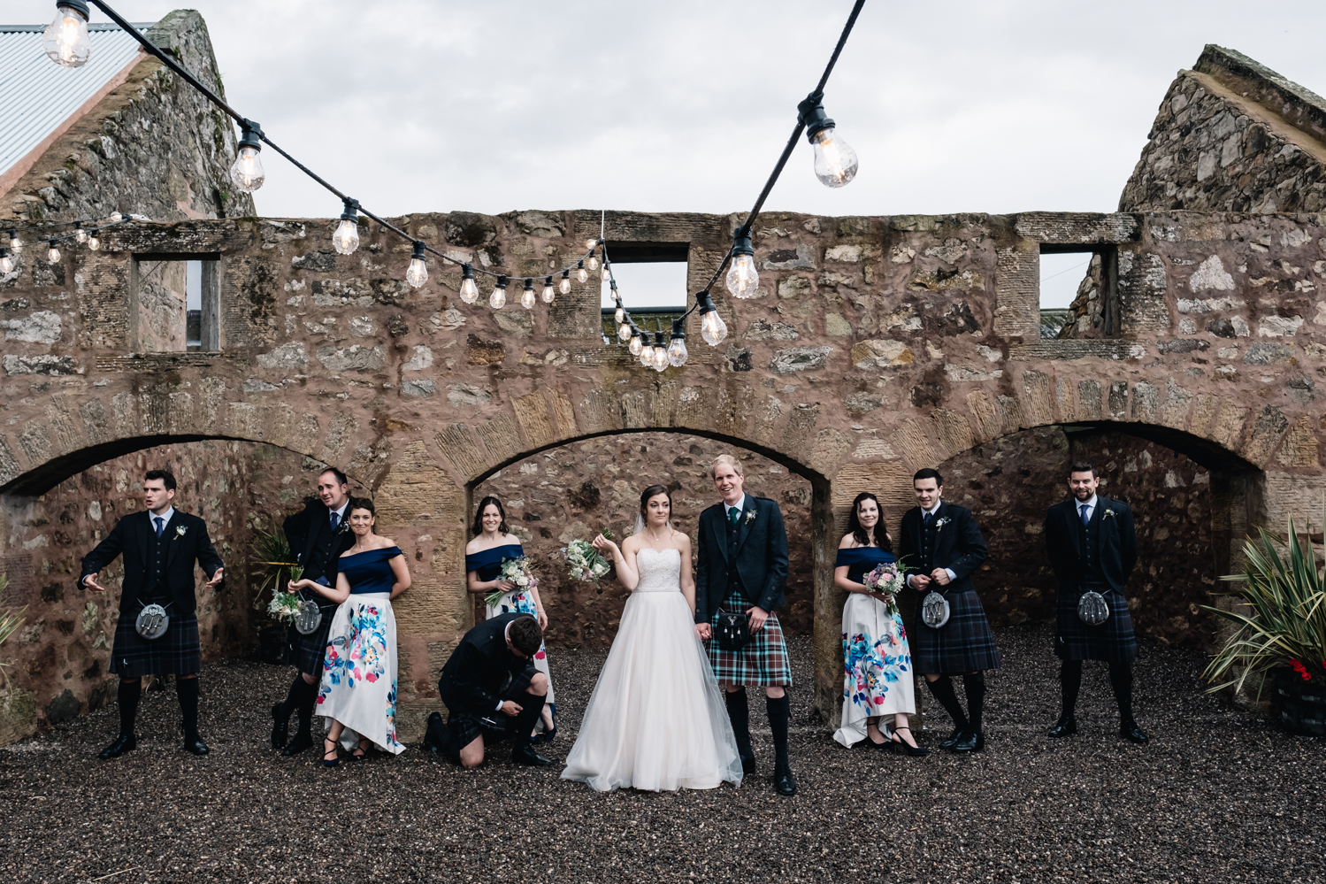 The bridal party are all standing with various expressions + stances in this unconventional bridal portrait.