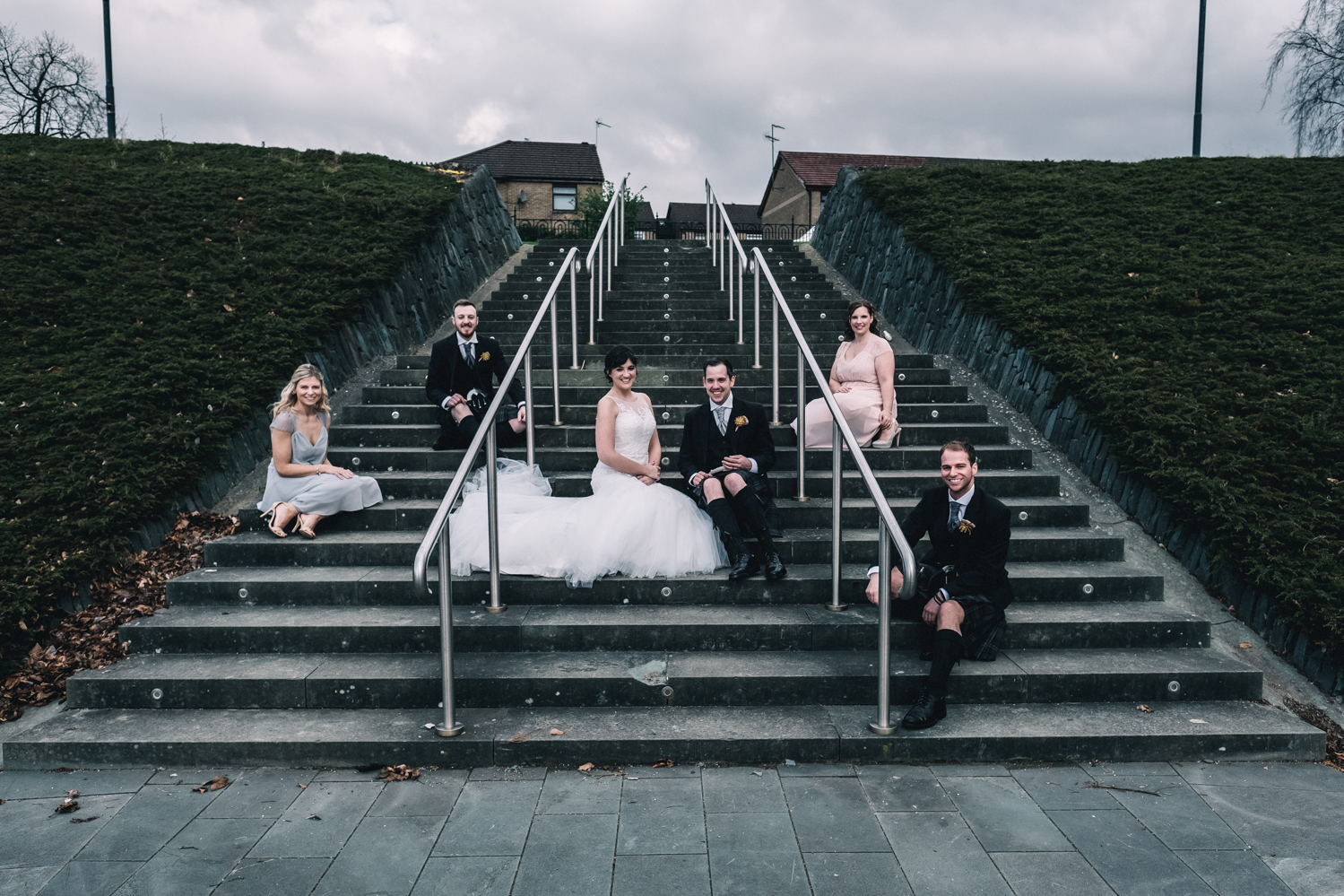 Bridal party sitting on stairs outside West on the Green.