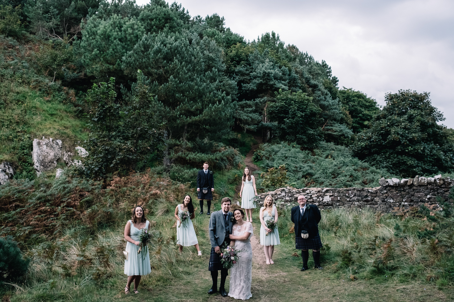 An unconventional bridal party group shot in a field.