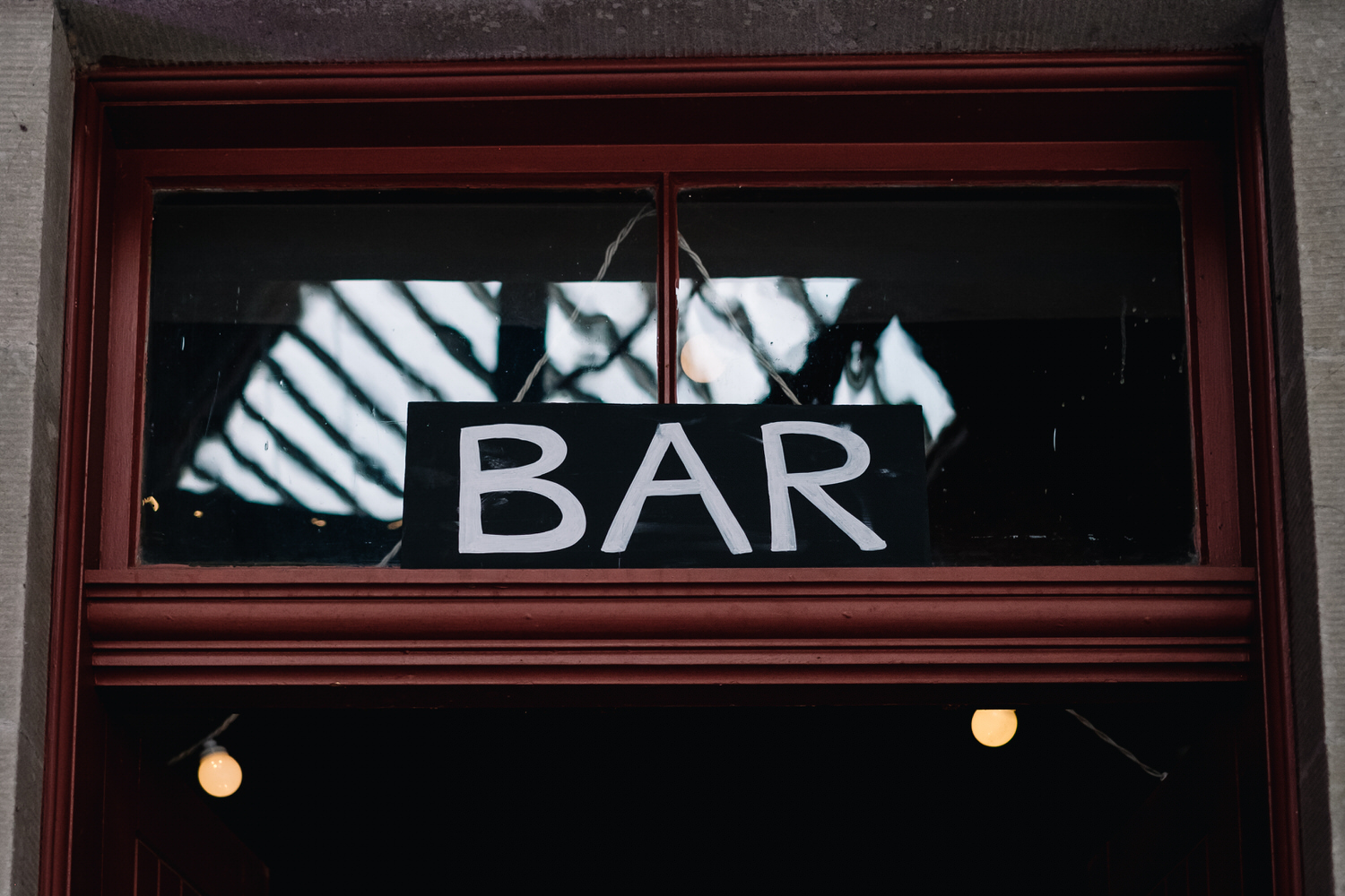 Bar sign hangs above the door of the bar's entrance.