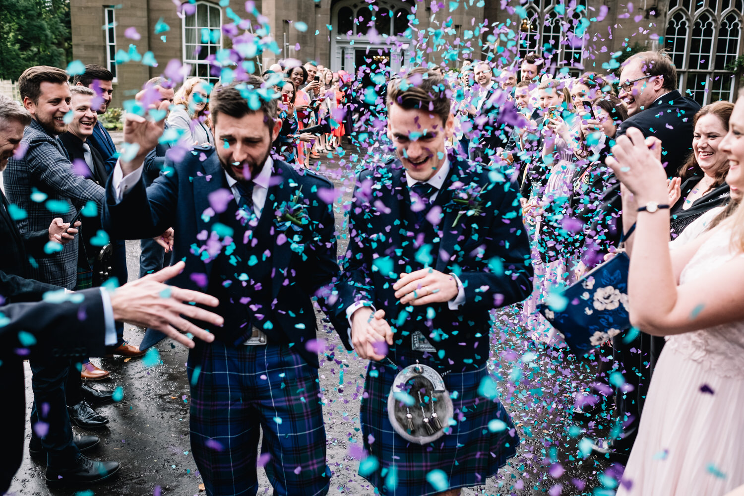 A couple laugh and run as they are showered with purple and blue confetti.