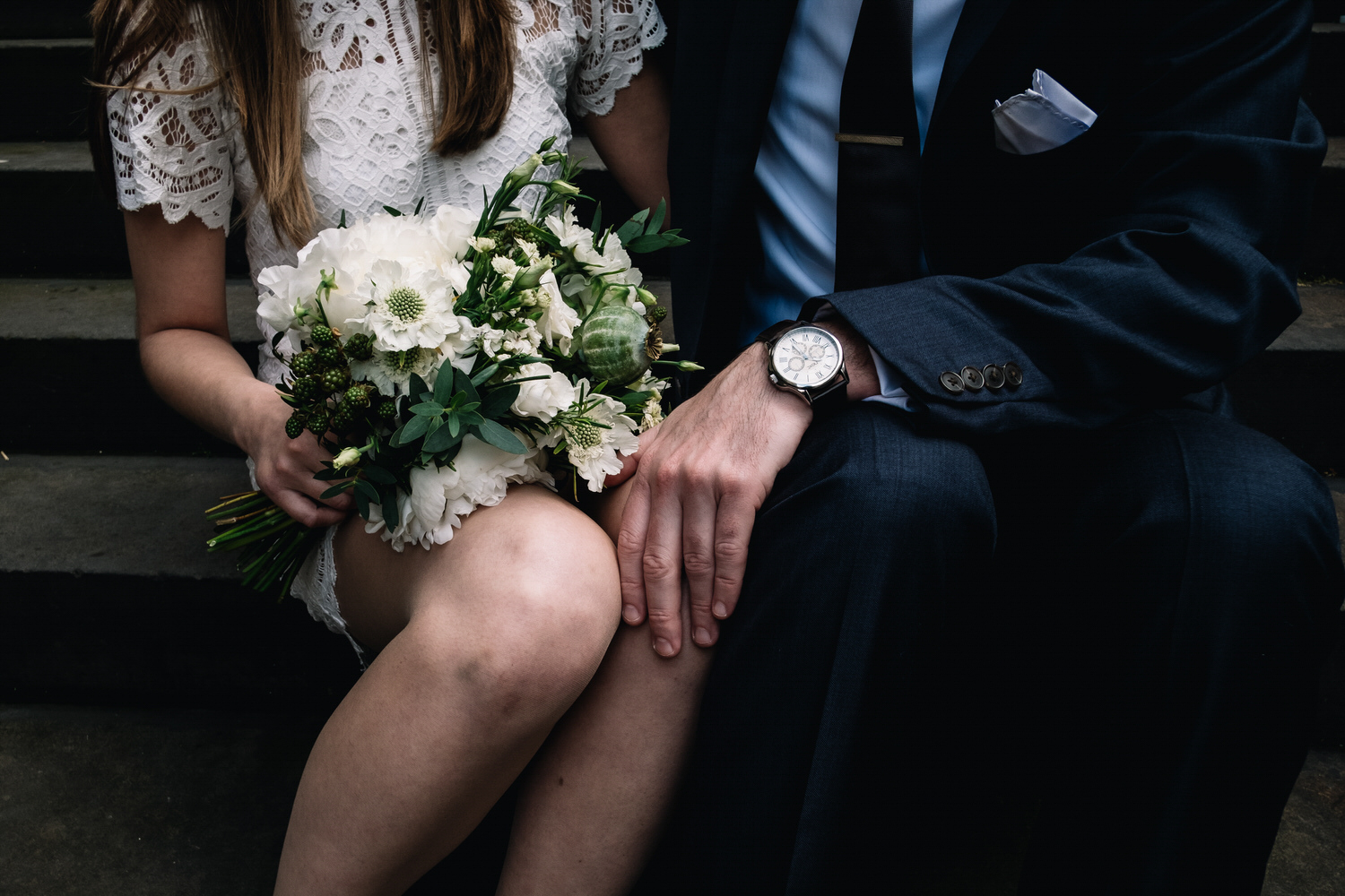 Groom's hand is placed on the bride's knee