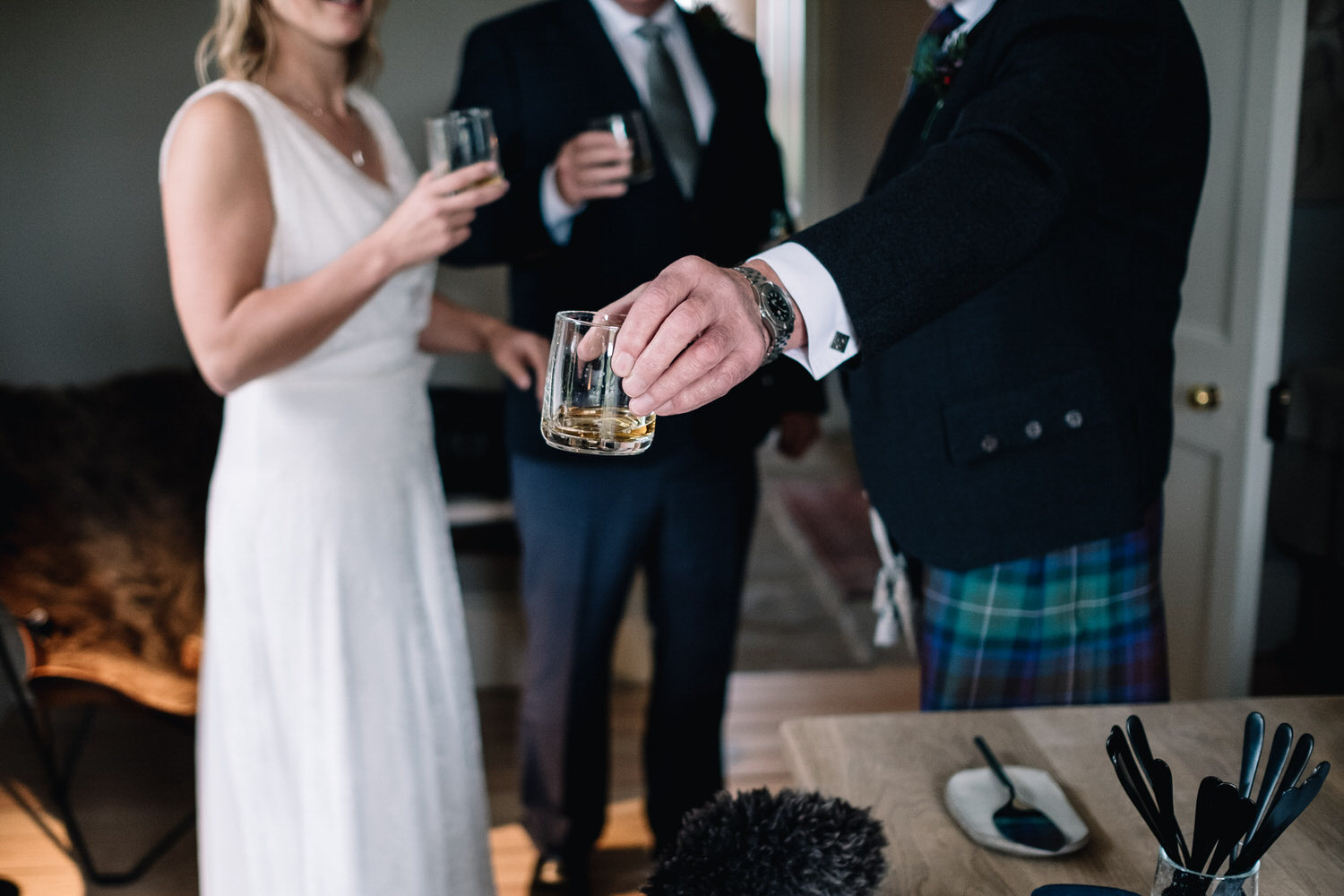 the groom holds a drink