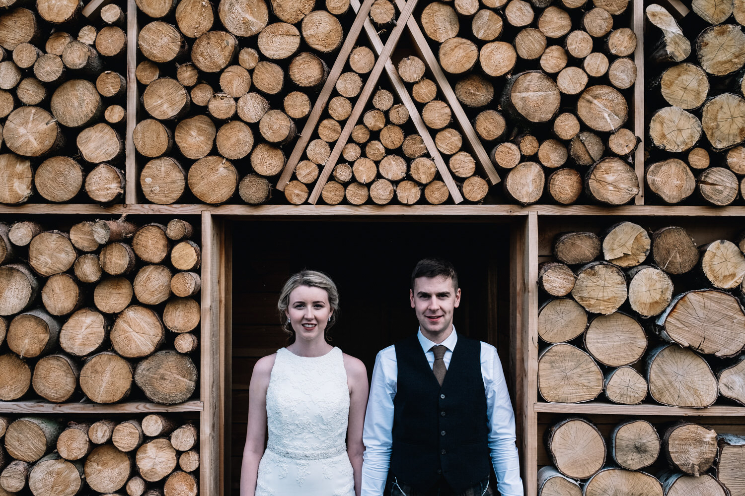 A couple stand holding hands at the log cabin at Guardswell Farm