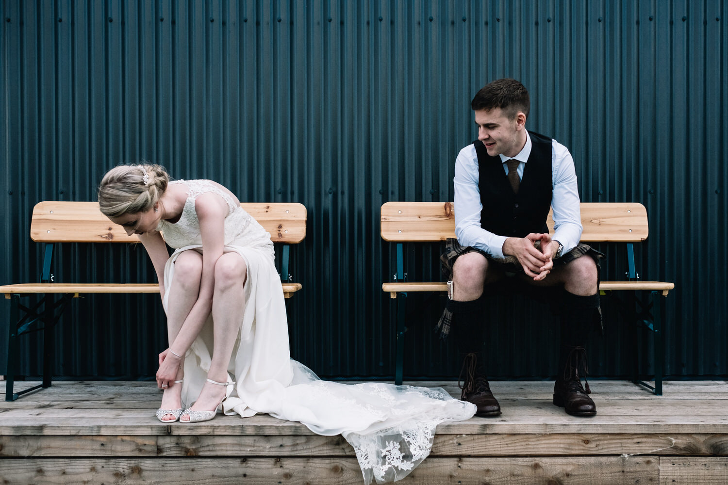 A couple sit on a bench