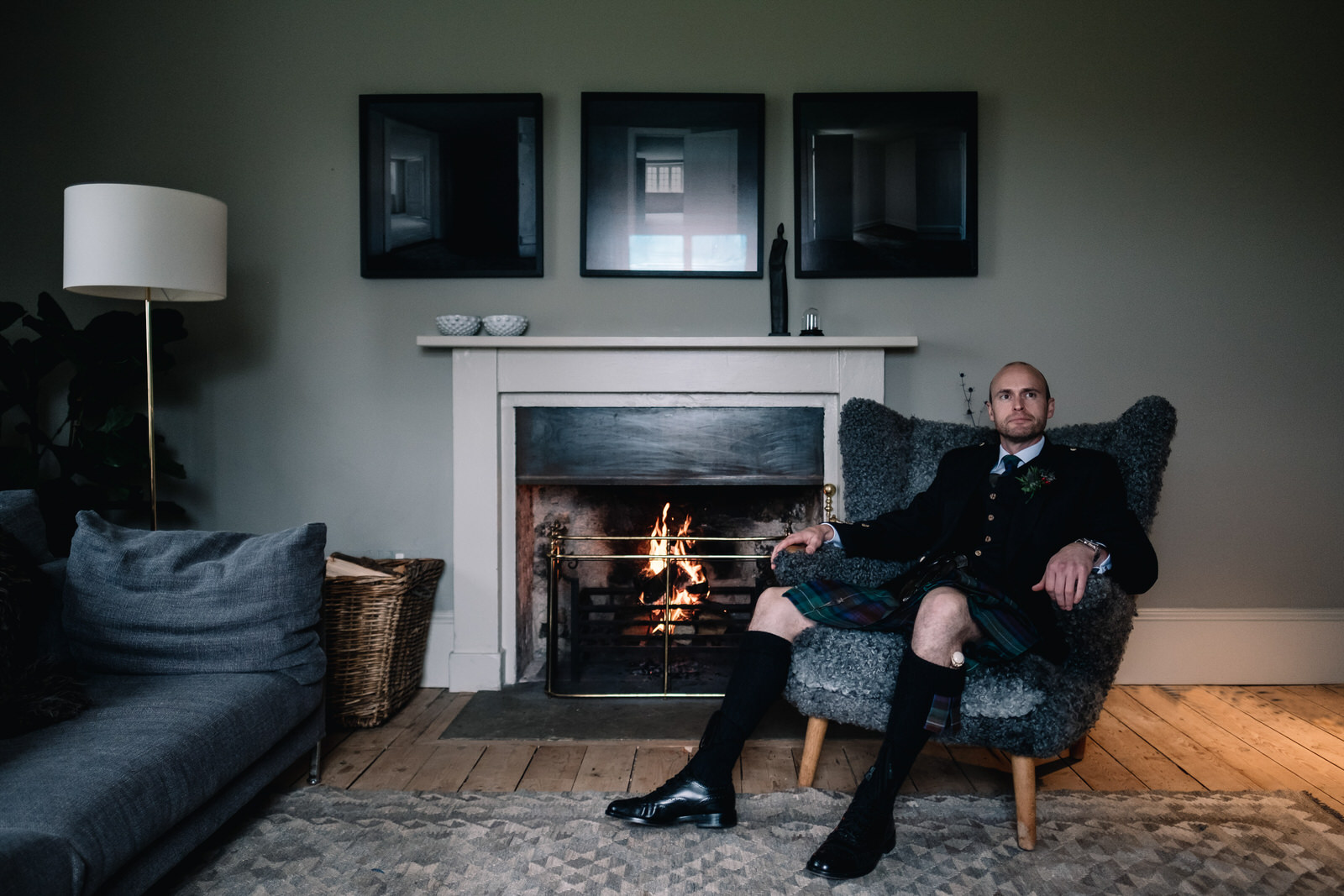 A kilted groom sits by the fire of the Killiehuntly Cottage