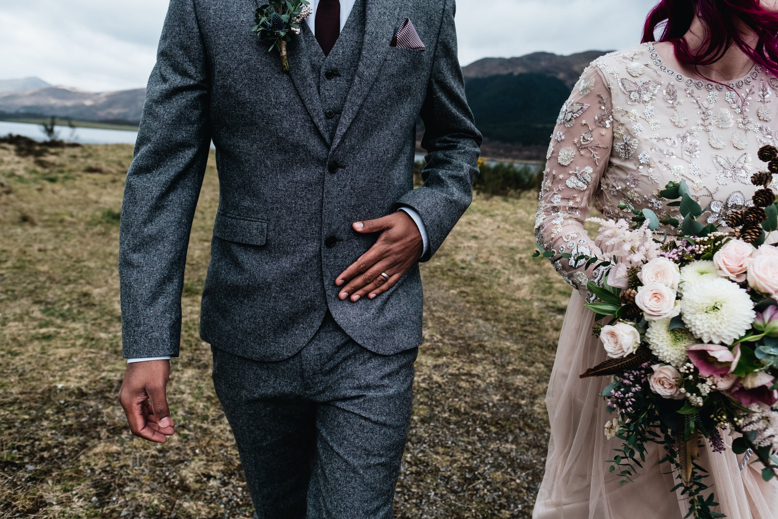 A groom walks alongside his bride who is carrying her flowers.