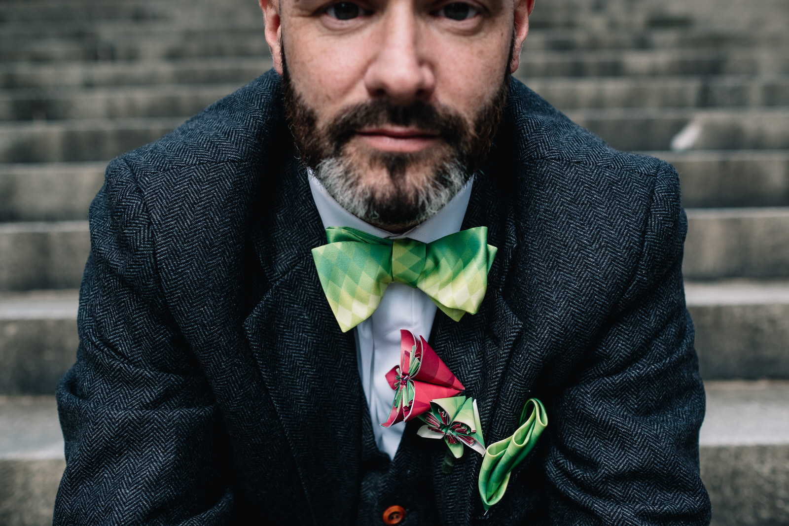 A groom is wearing a brightly coloured bow tie.