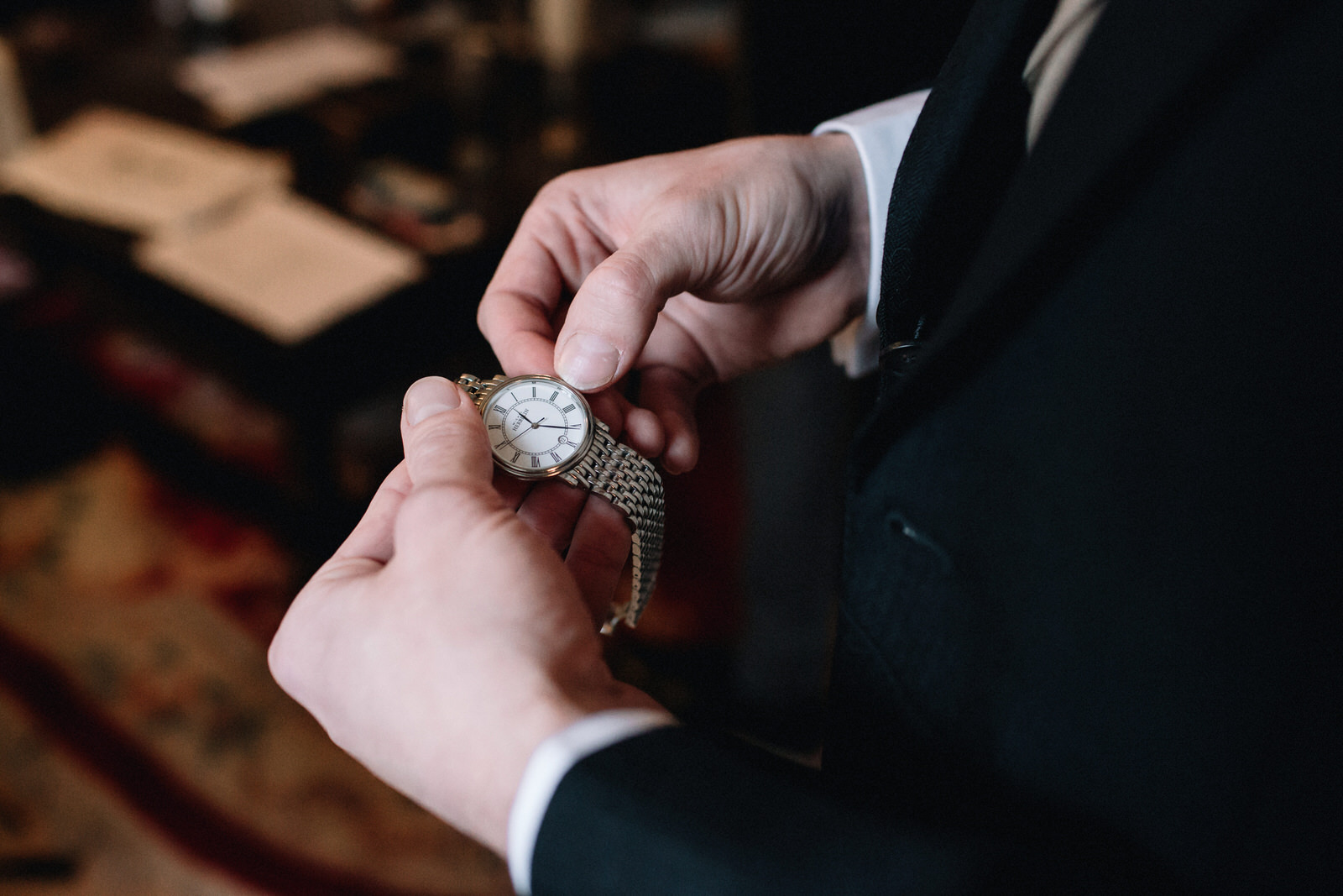 A groom is setting the time on his watch on the mornig of his wedding.