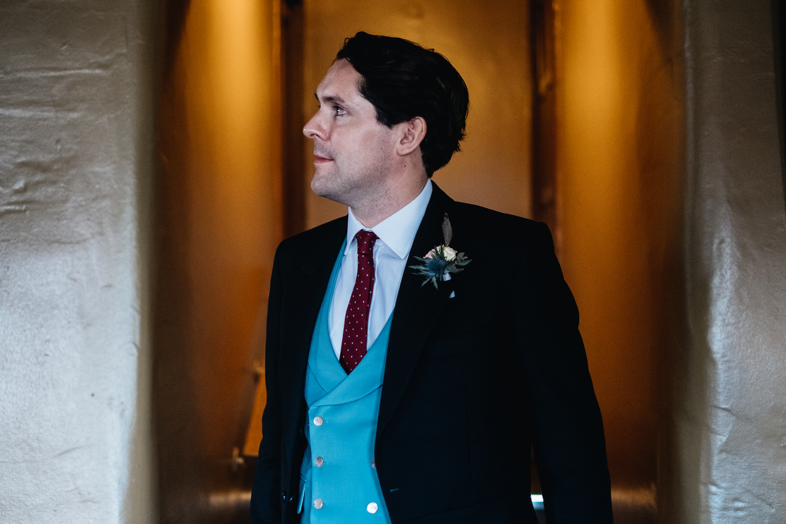 A groom stands by an oragne light which contrasts with his blue waistcoat.