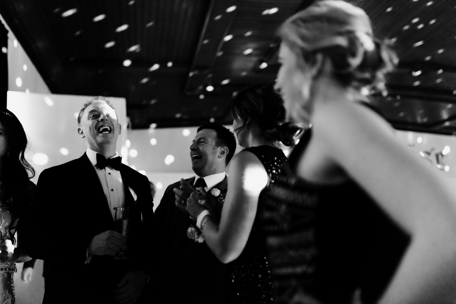 A groom laughs with guests.