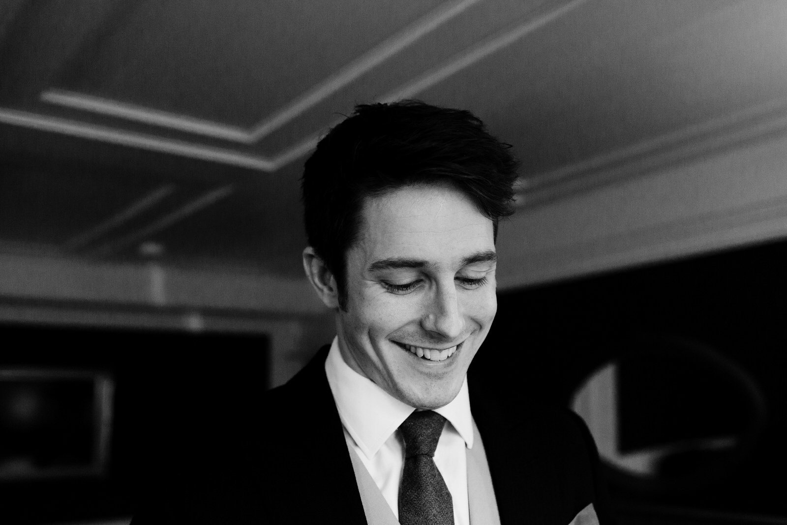 A groom is looking down and smiling.