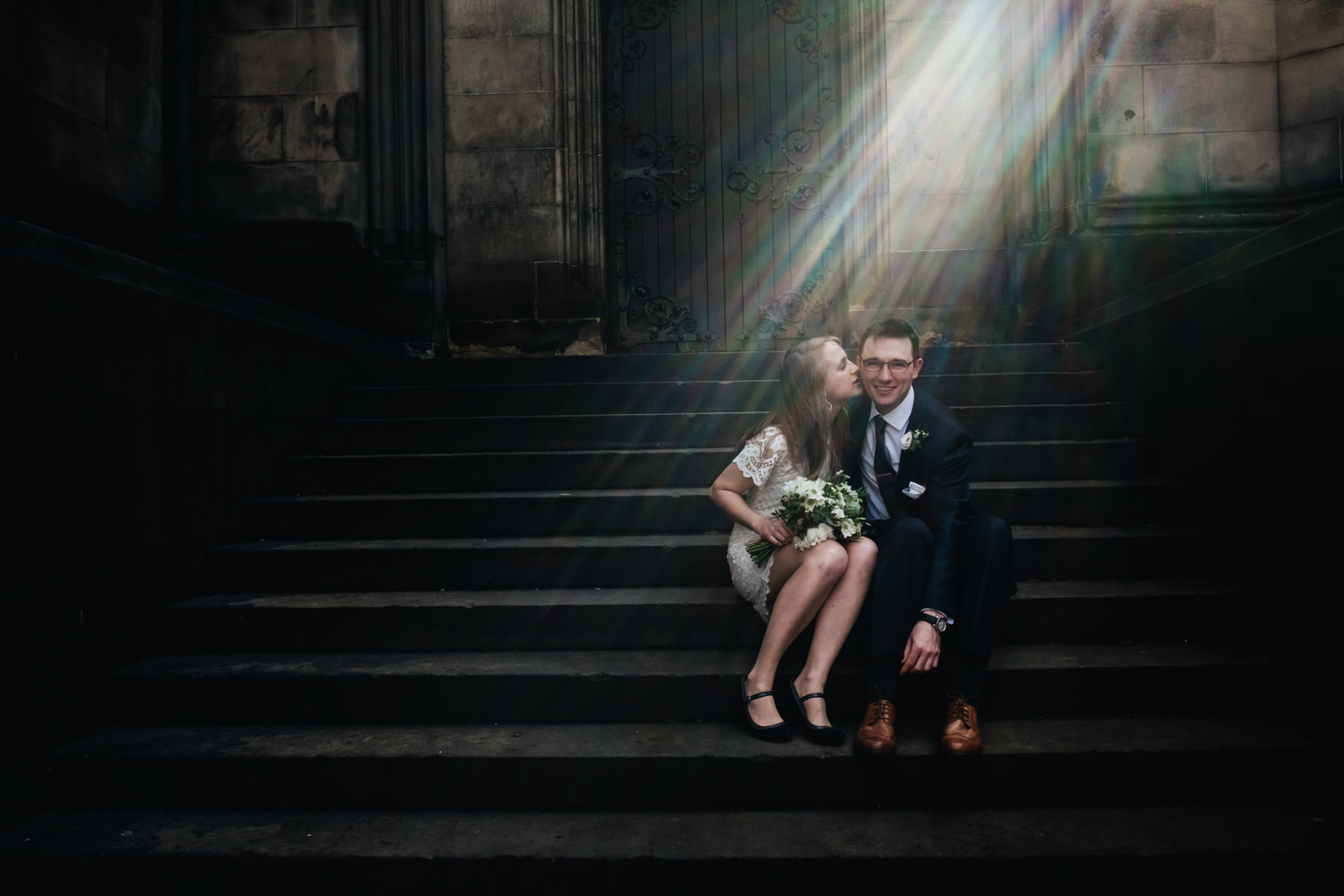 A newly eloped couple sit on stairs smiling at each other.