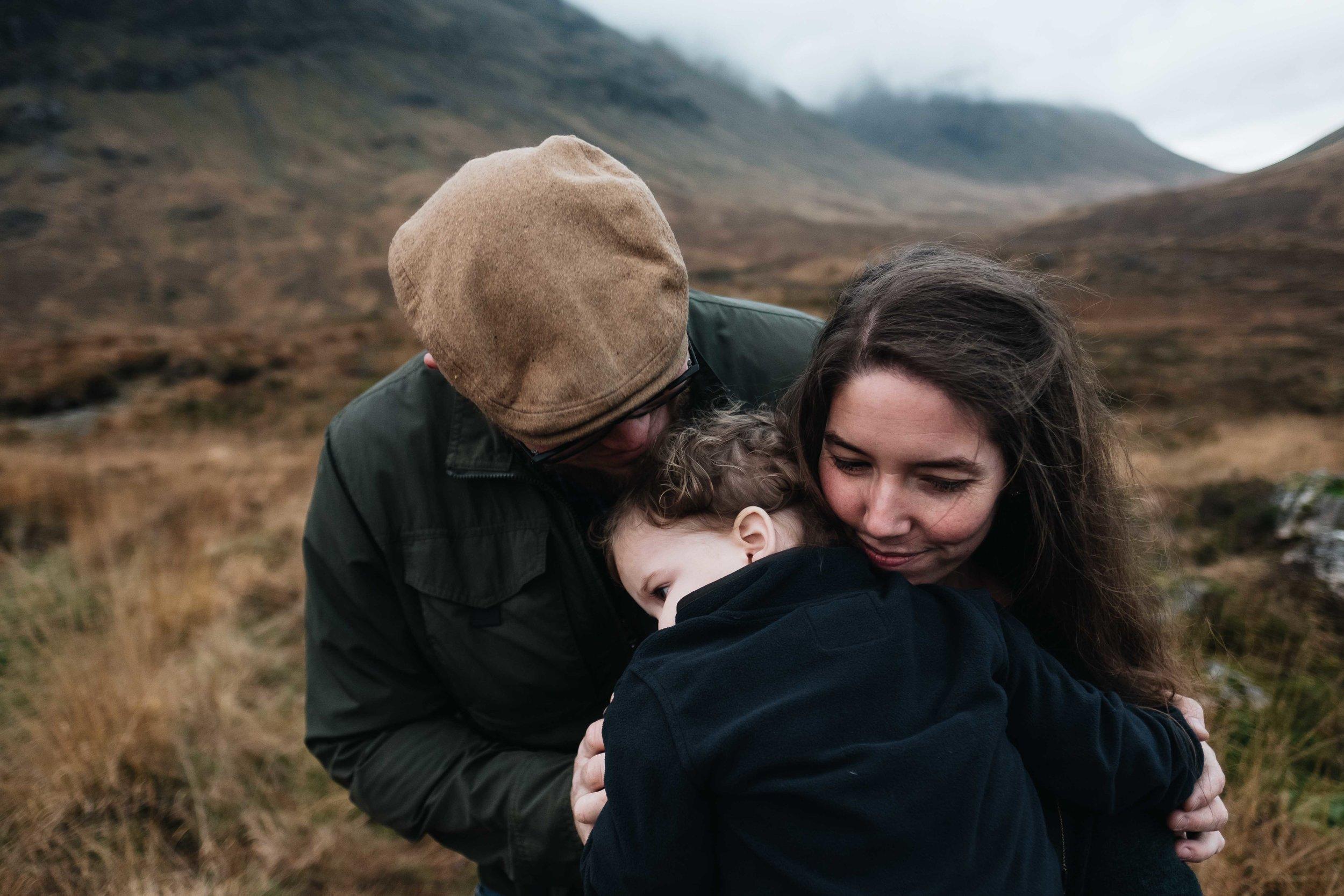 parents hug their toddler boy