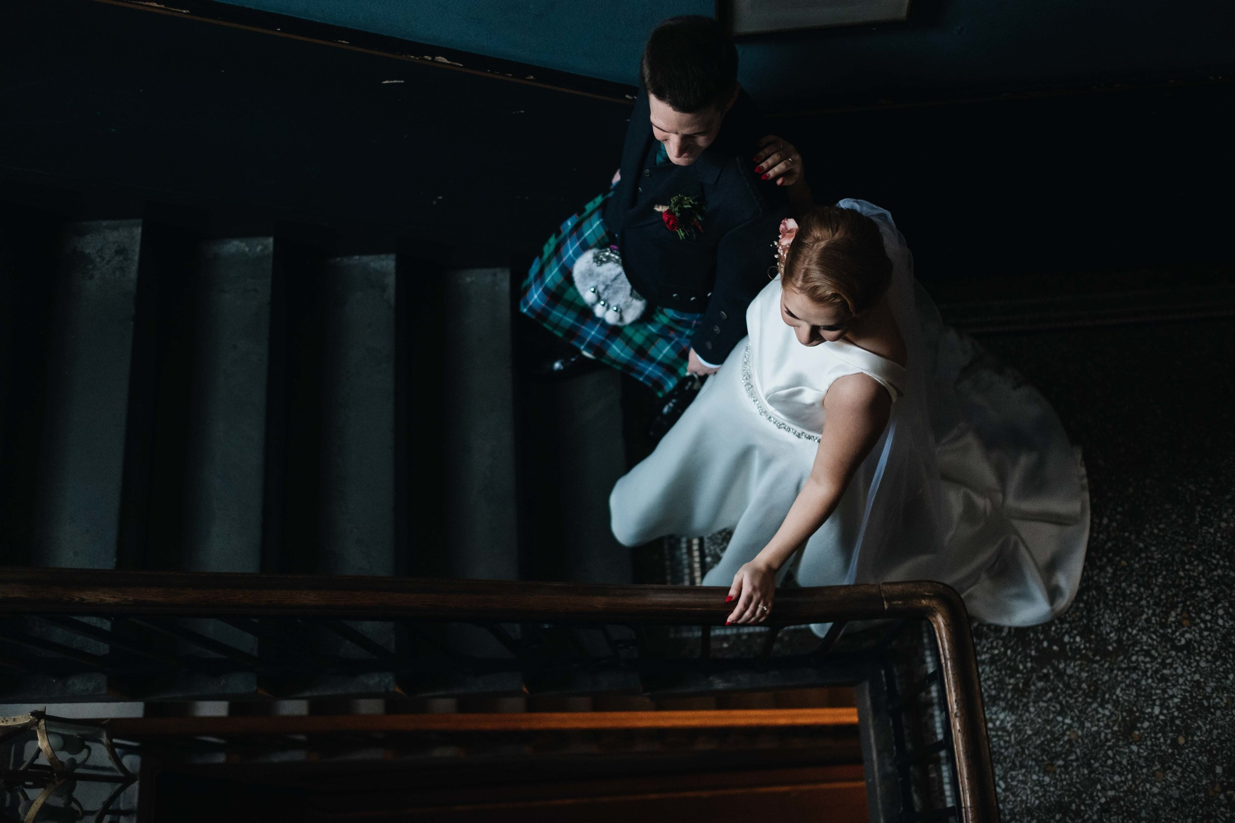bride and groom standing at the bottom of the stair case.