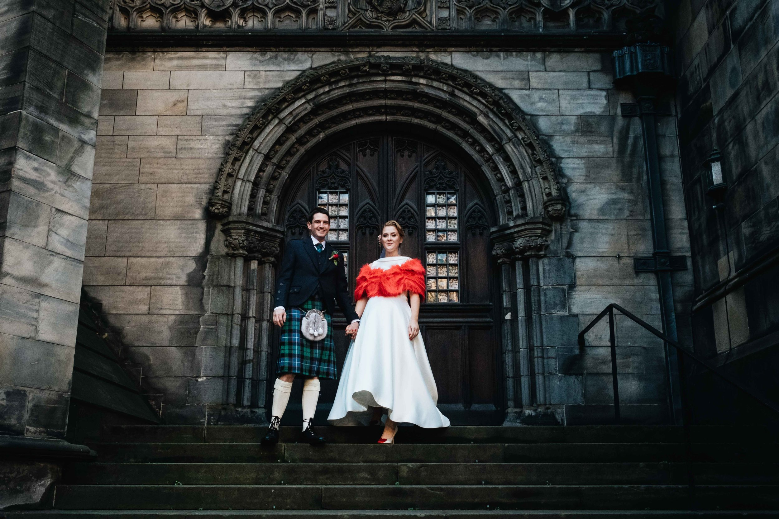 newly married couple standing on stairs at st giles chapel in Edinburgh
