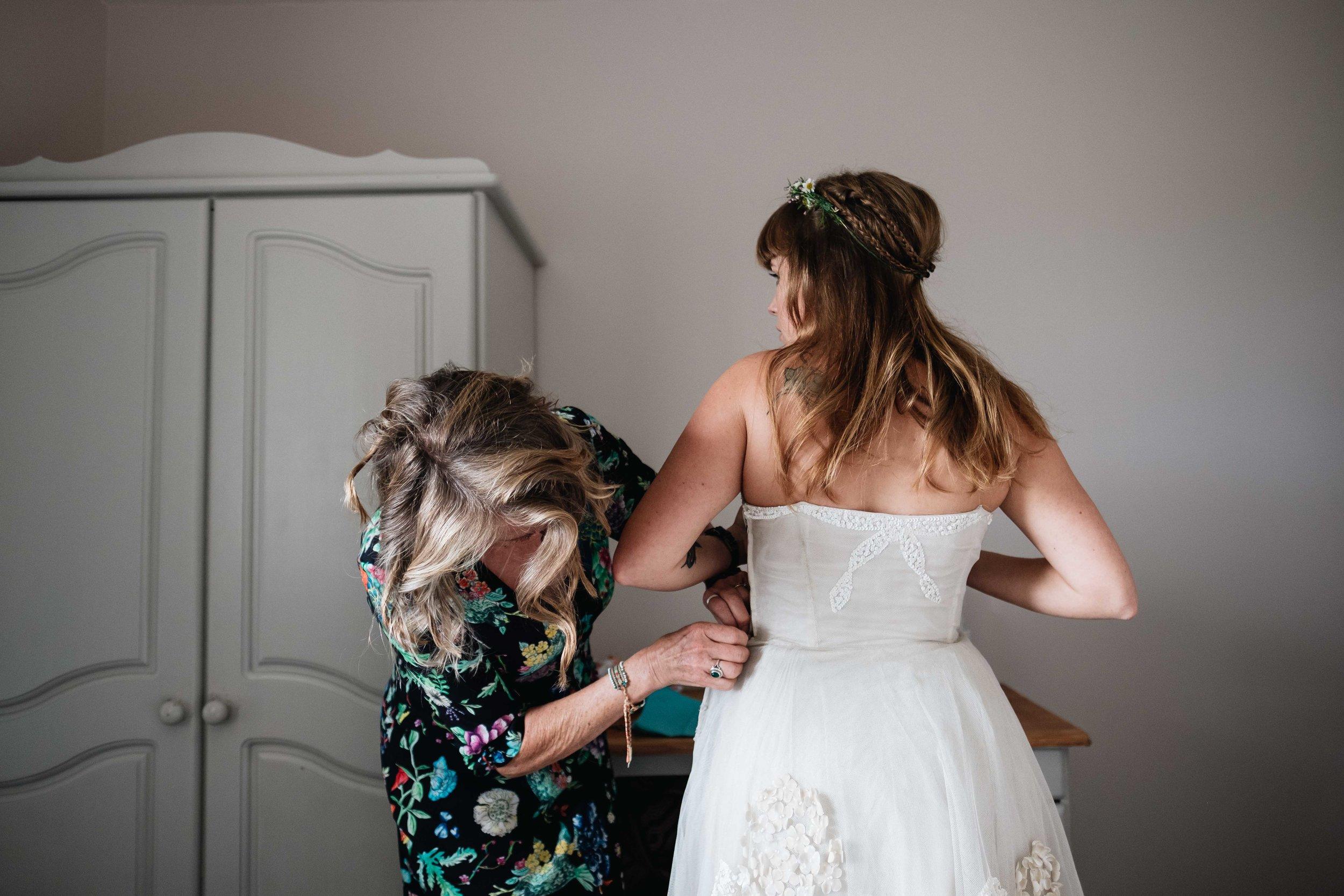 Mum helping bride get her dress on