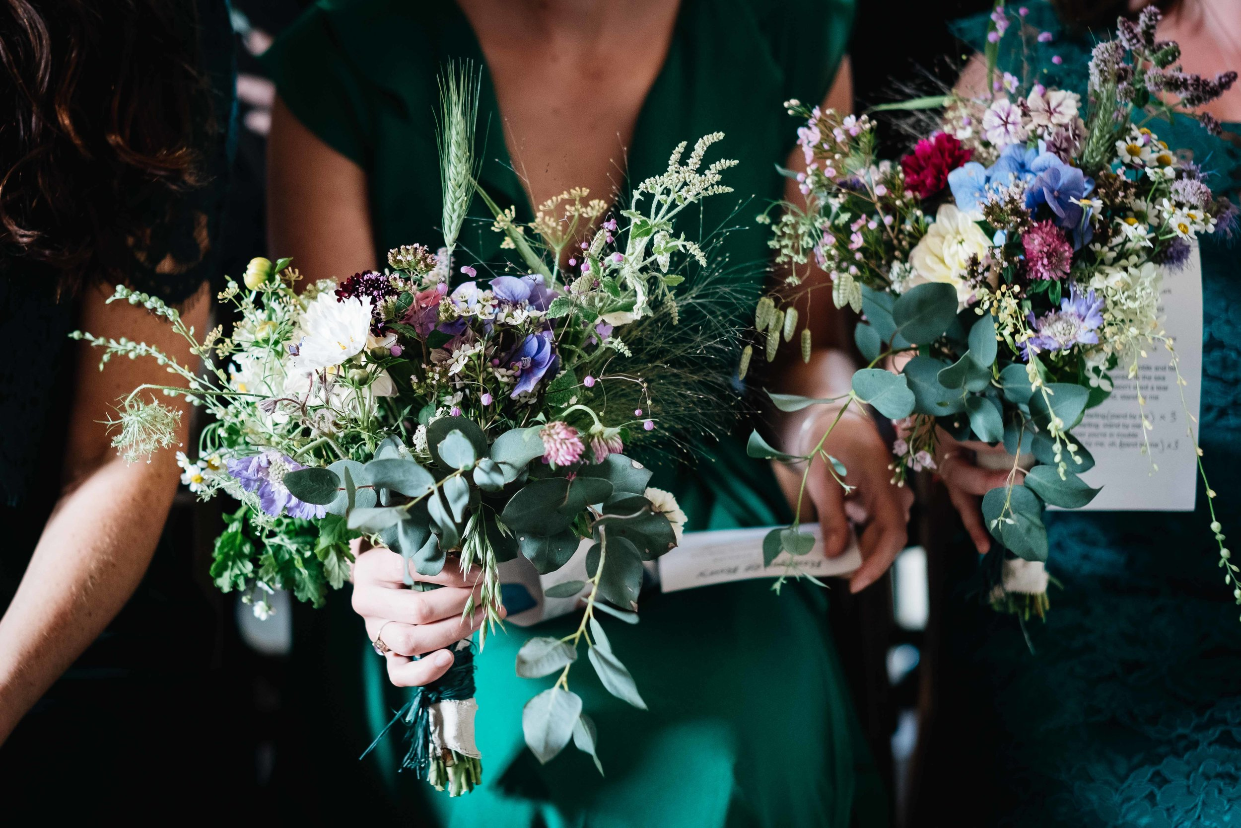 bridesmaids holding their flowers during the ceremony