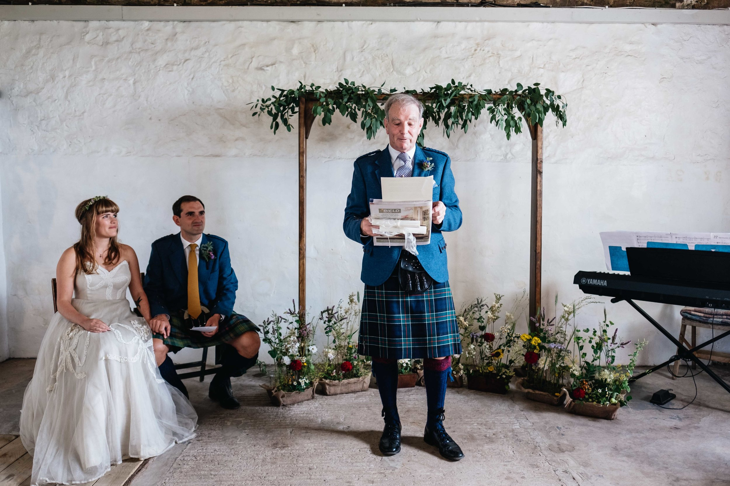 groom's father is reading during the ceremony